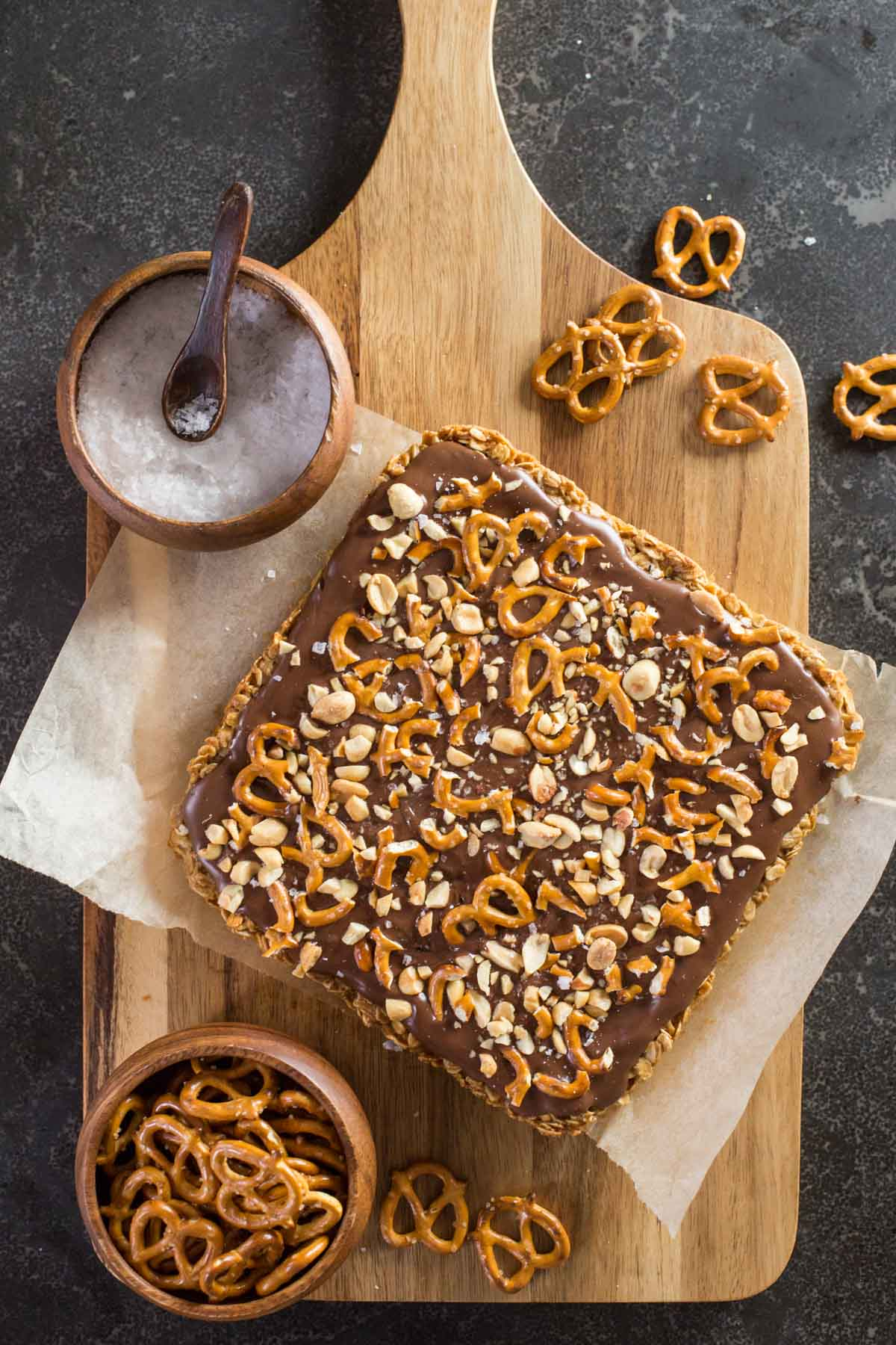 A slab of Oh Henry Bars uncut from a top down view, topped with peanuts and pretzels