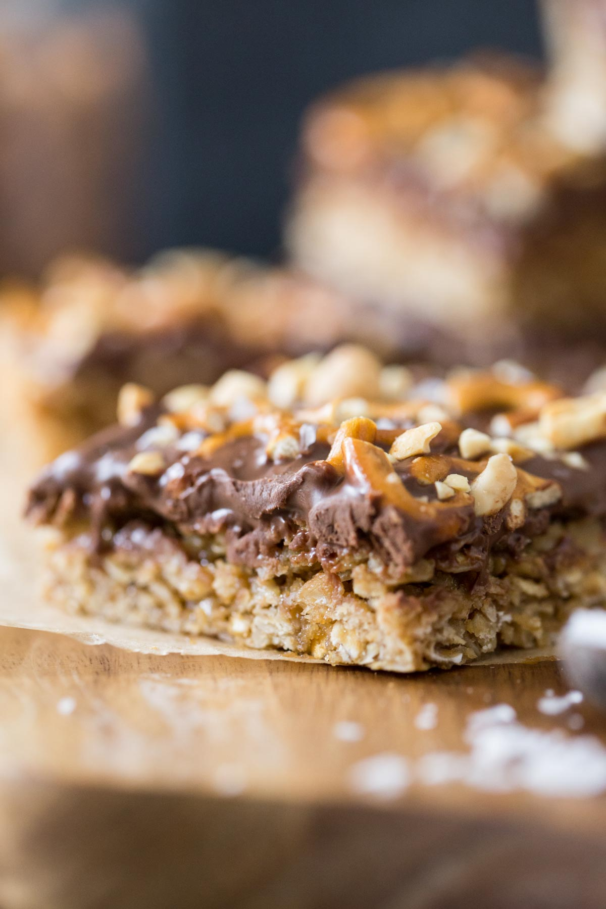 A close up view of the oatmeal and peanut butter chocolate layer of an Oh Henry Bar from the side view