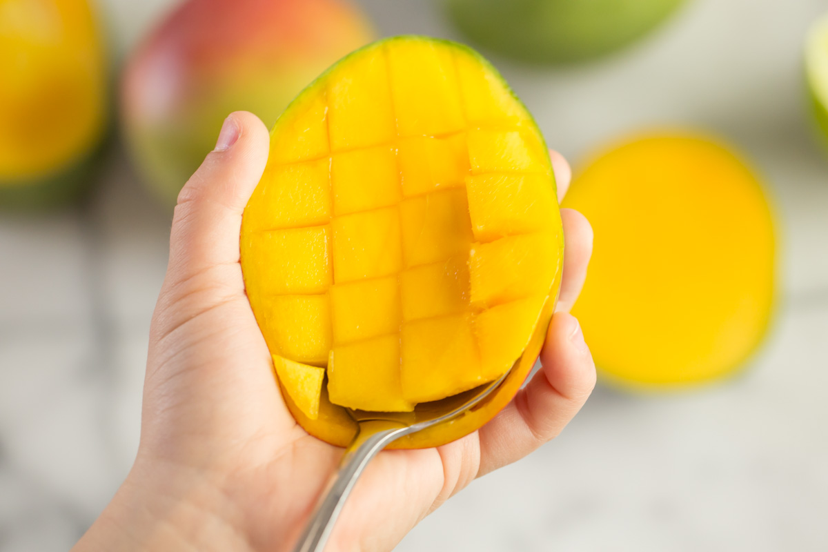 Step 5 of how to cut a mango - use a large spoon to detach the flesh from the skin and scoop out the cubes.