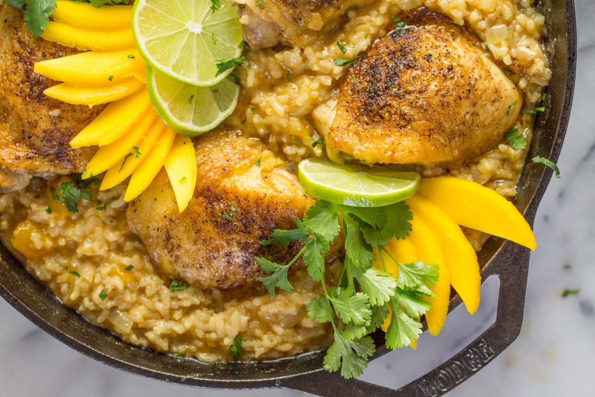 We've got crispy chicken cooked on the bone so it stays nice and juicy, and creamy rice with lots of onions, garlic, chili powder, and lime. Serve it with fresh slices of mango, lots of cilantro and freshly squeezed lime juice.
