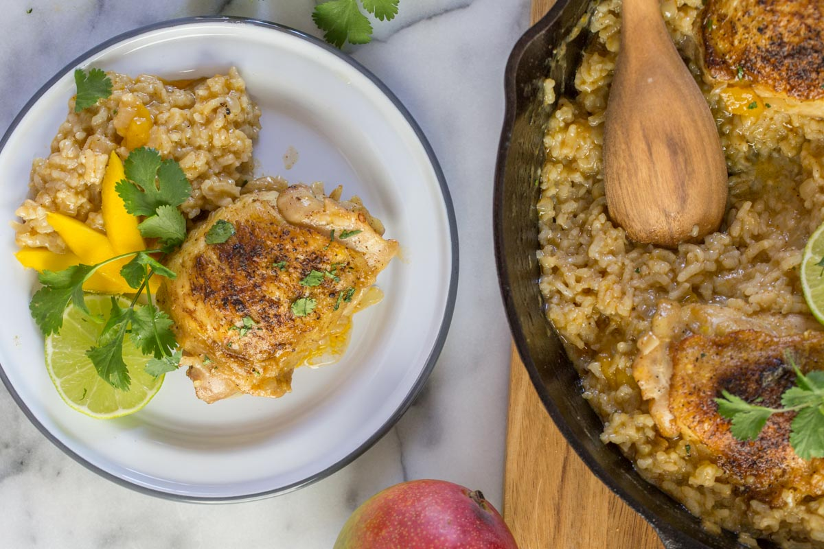 A serving of Chili Lime Mango Chicken and Rice on a plate, garnished with fresh cilantro, mango and lime slices, sitting next to the cast iron skillet of Chile Lime Mango Chicken and Rice.