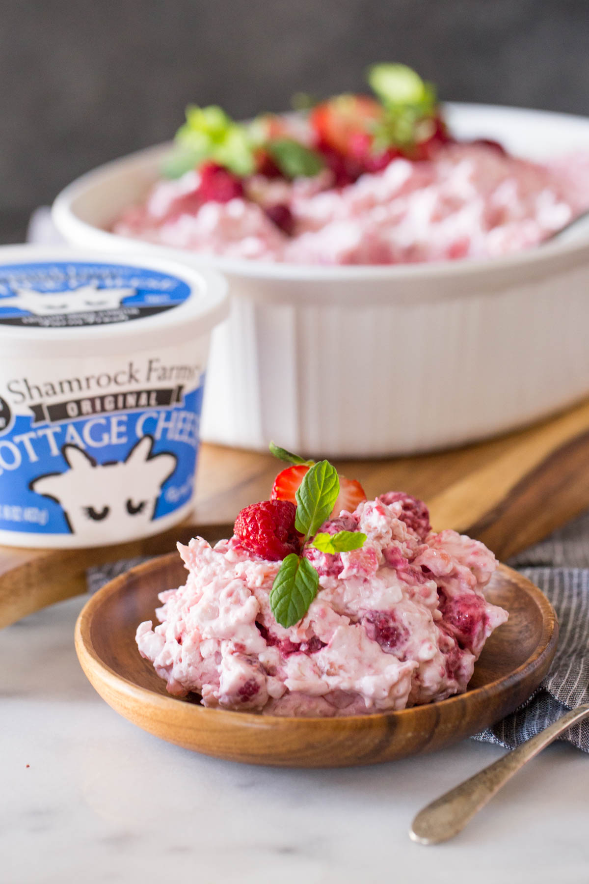 Very Berry Fluffy Salad dished out into a bowl with Shamrock Farms cottage cheese in the background.