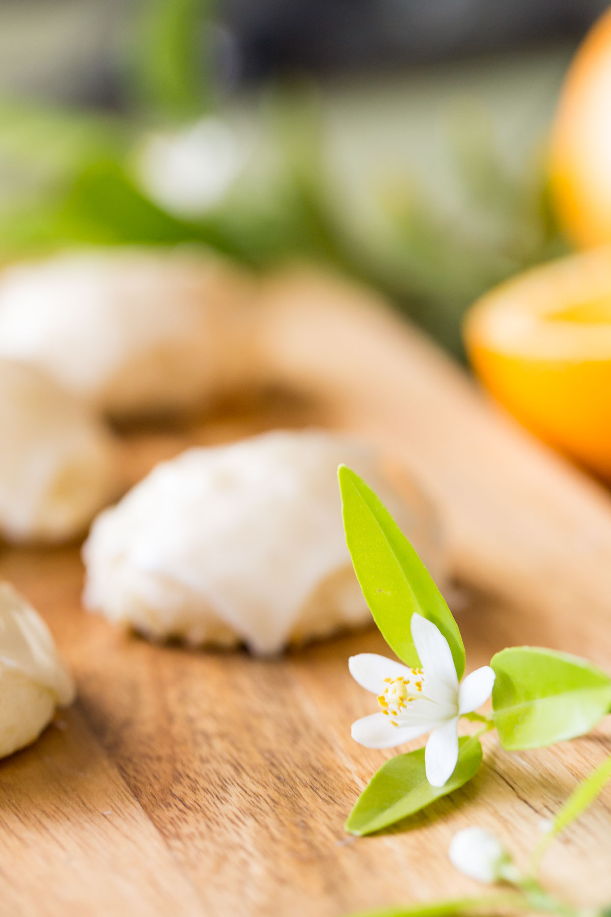 A close up shot of an orange blossom with cookies blurred in the background on a wooden cutting board.
