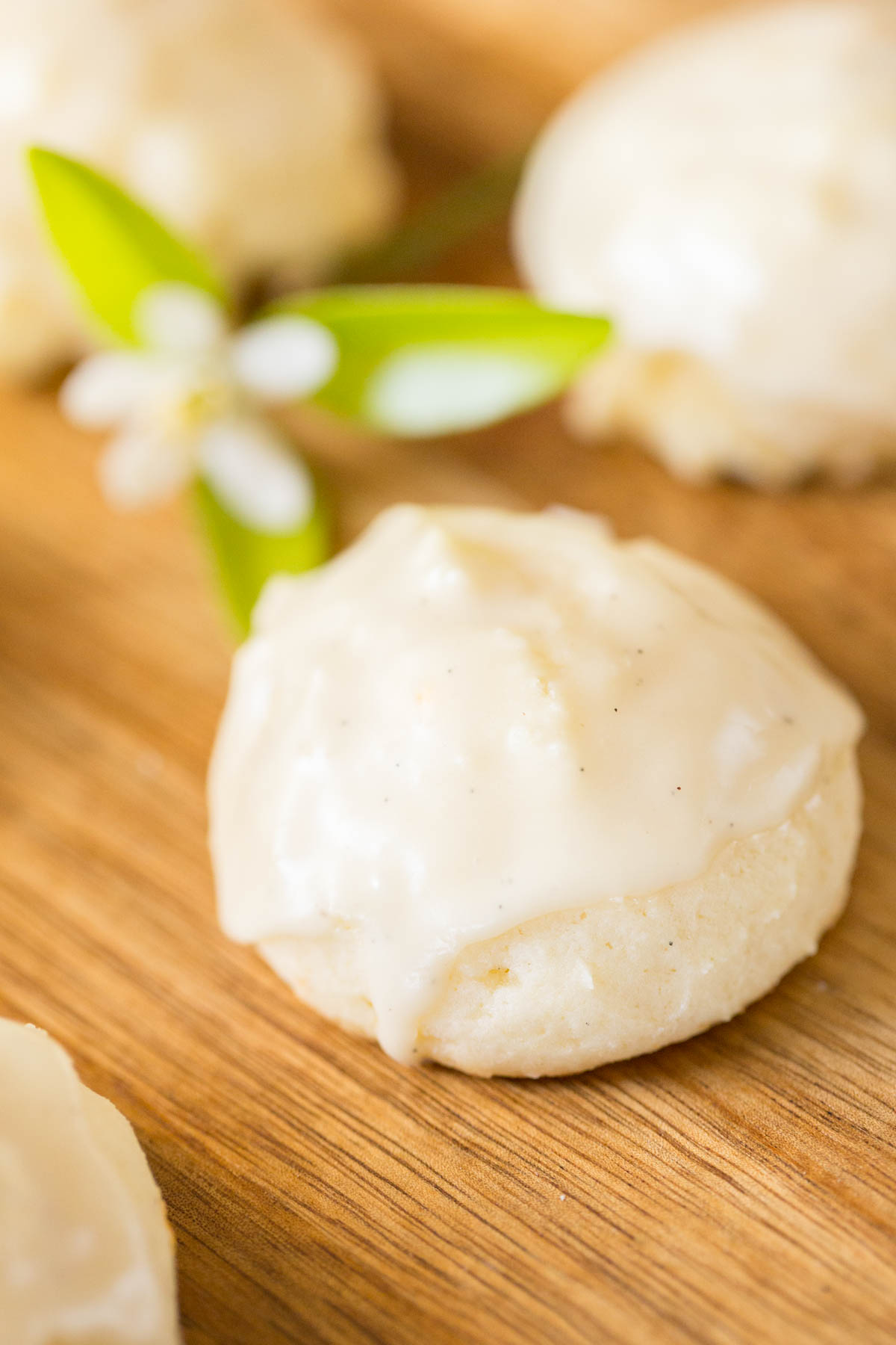 A close up shot of an Orange Ricotta Cookie with a vanilla glaze on top.