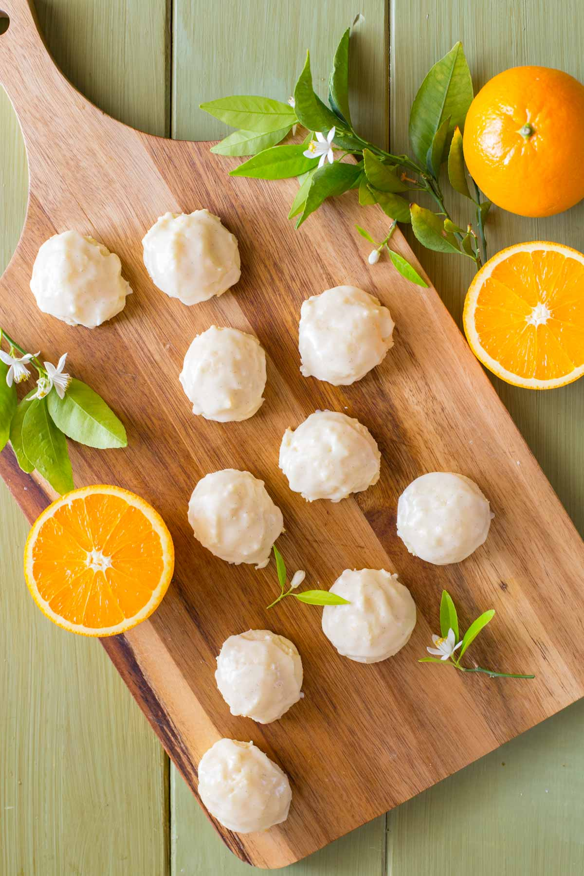 Orange Ricotta Cookies and sliced oranges with orange blossoms shot from above on a wooden cutting board.