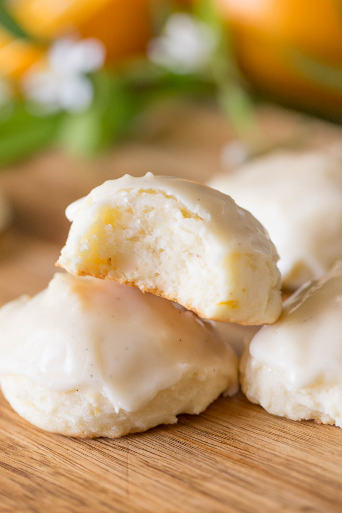 Stacked Orange Ricotta cookies with a bite missing, showing a close up on the inside of the cookie.