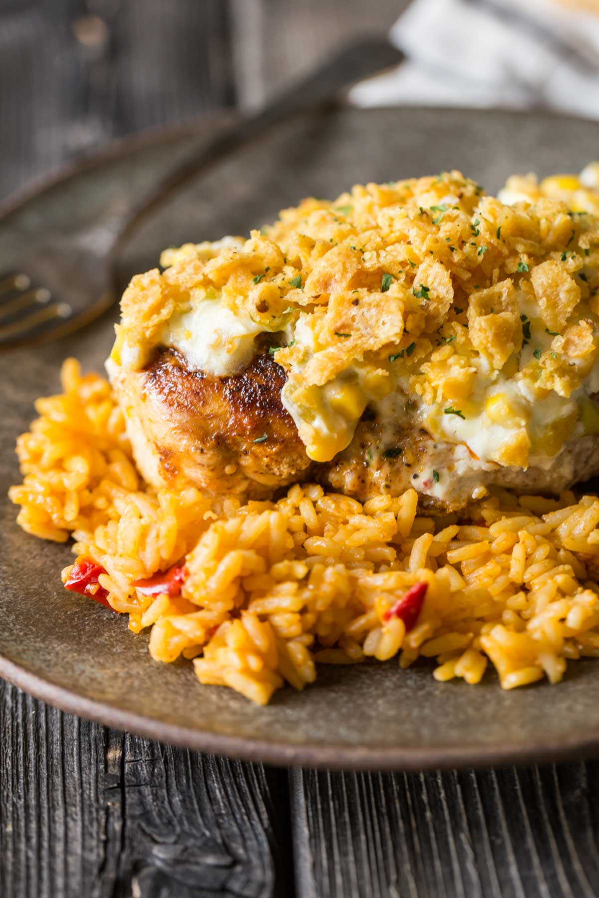 Close up of Creamy Cheesy Frito Chicken Skillet served over rice on a plate.
