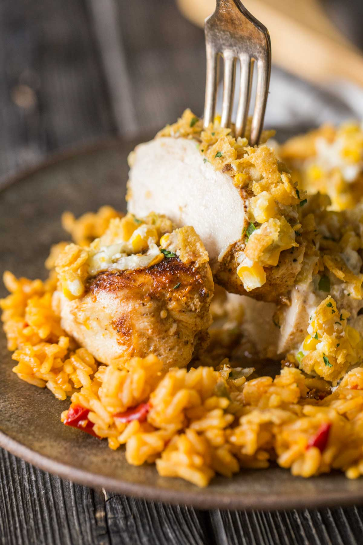 Slice of Creamy Cheesy Frito Chicken Skillet lifted off a plate with a fork.