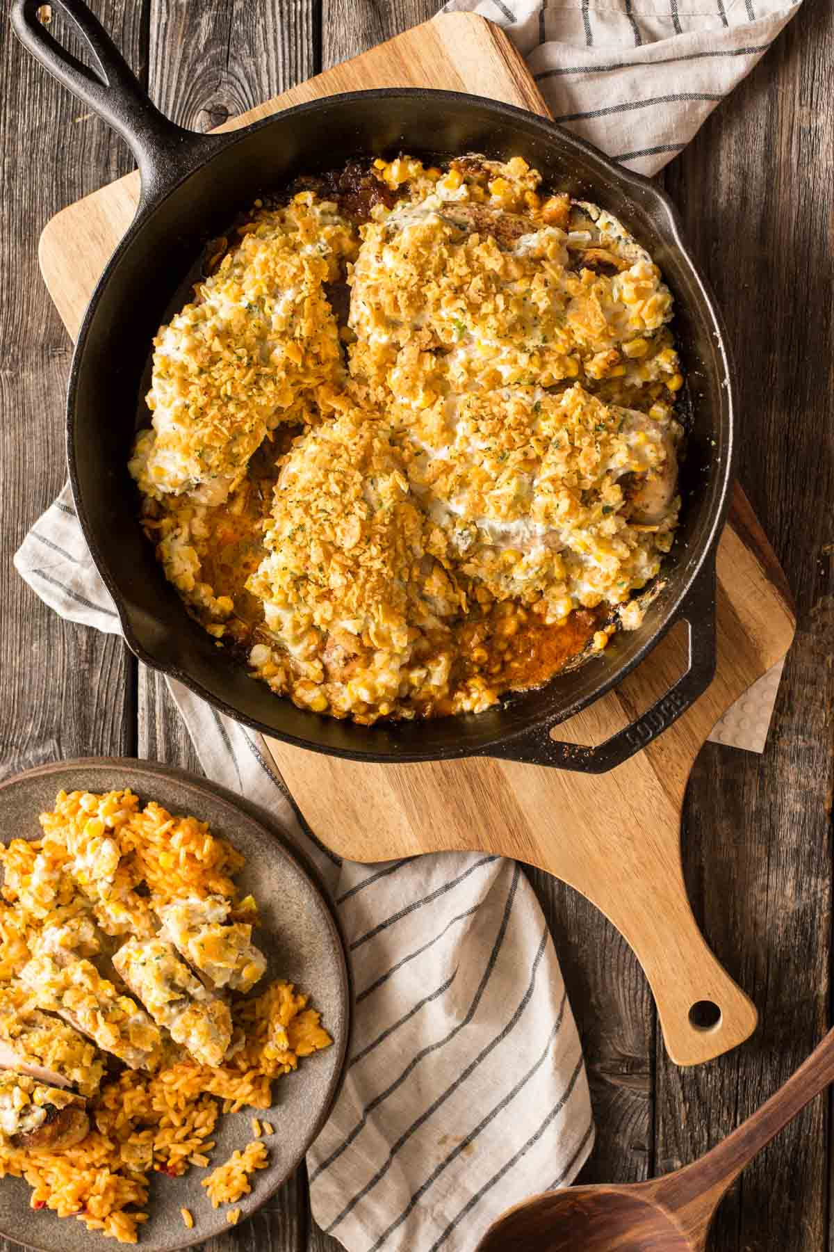 Overhead shot of cast iron skillet with Creamy Cheesy Frito Chicken Skillet on a cutting board.