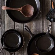 Various sizes of cast iron skillets on a wooden board.