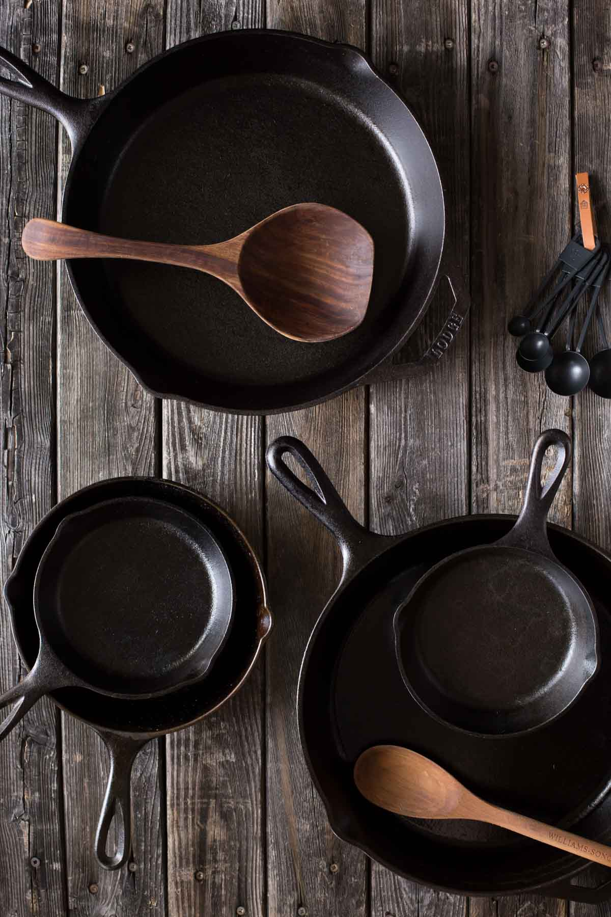 A top down view of various sizes of cast iron skillets with wooden spoons.
