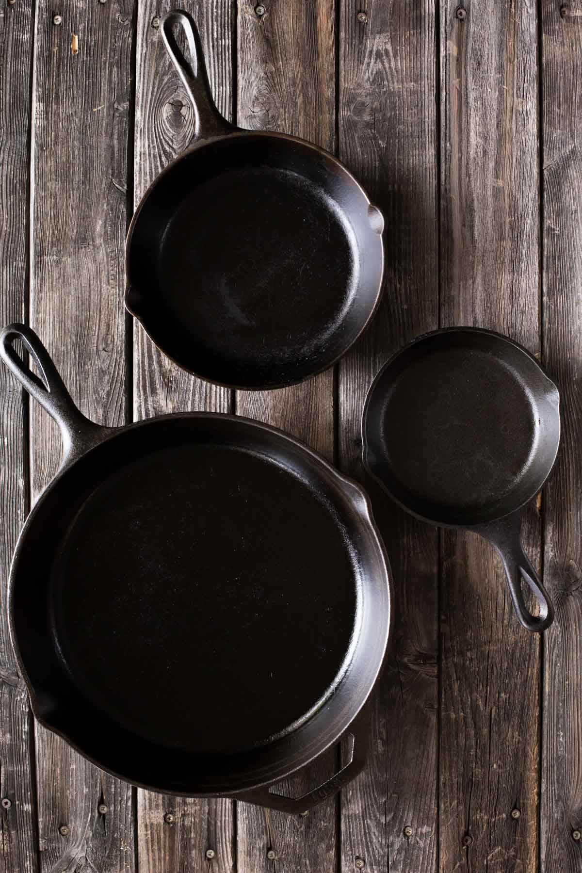 A top down view of a small, medium, and large sized cast iron skillet on a wooden background.