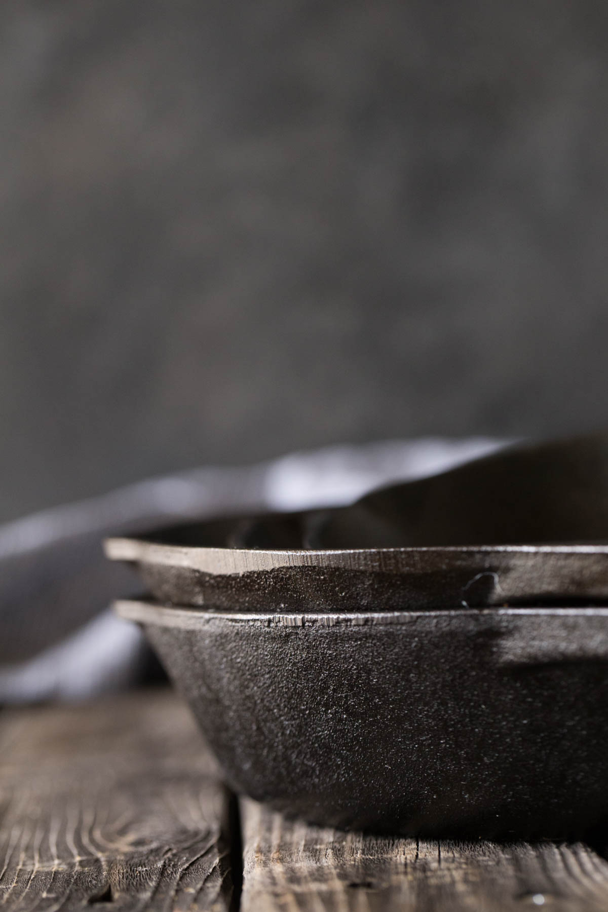 A close up view of cast iron skillets from the side with a grey background.