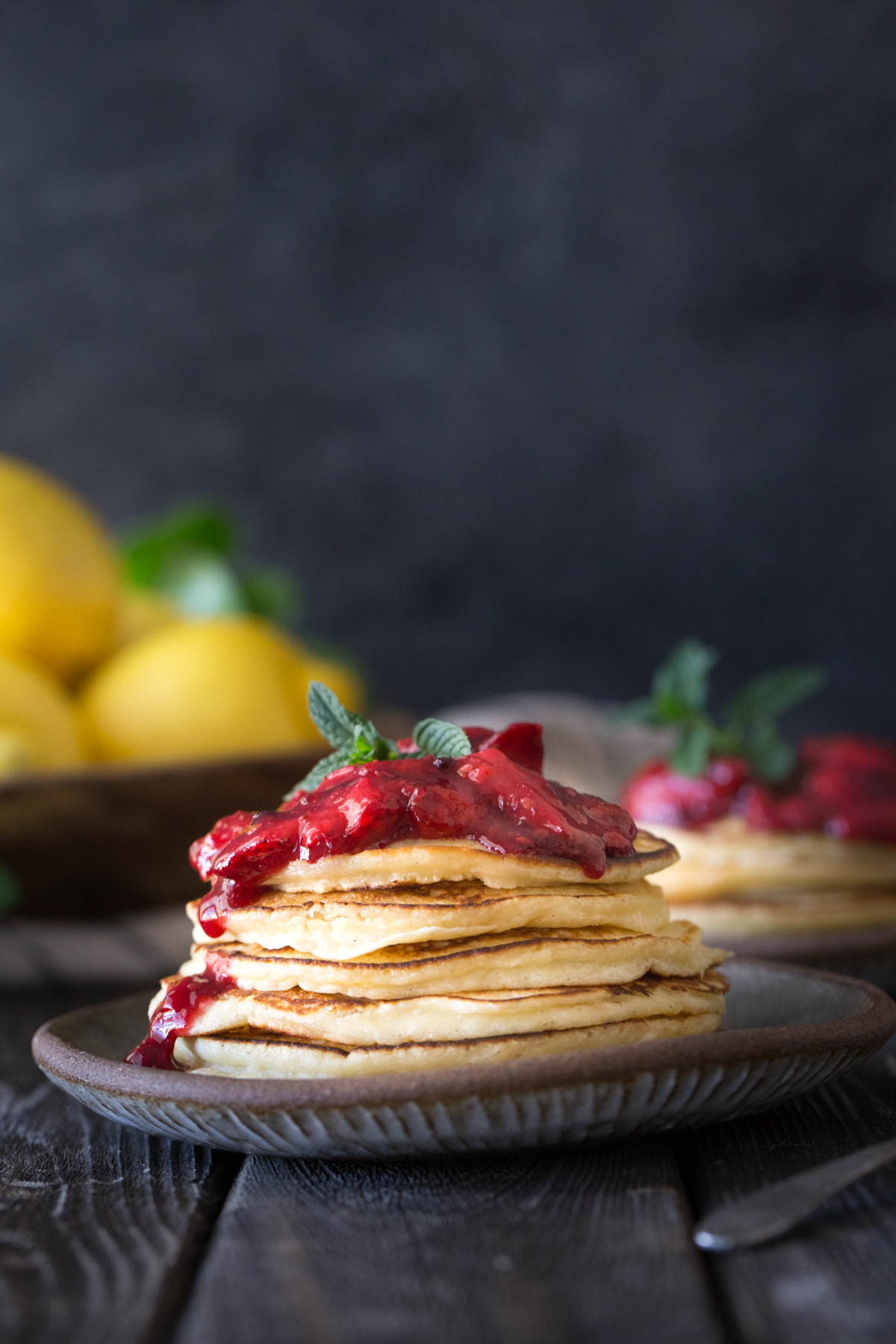 A stack of Lemon Ricotta pancakes with fresh berry sauce on a grey background.