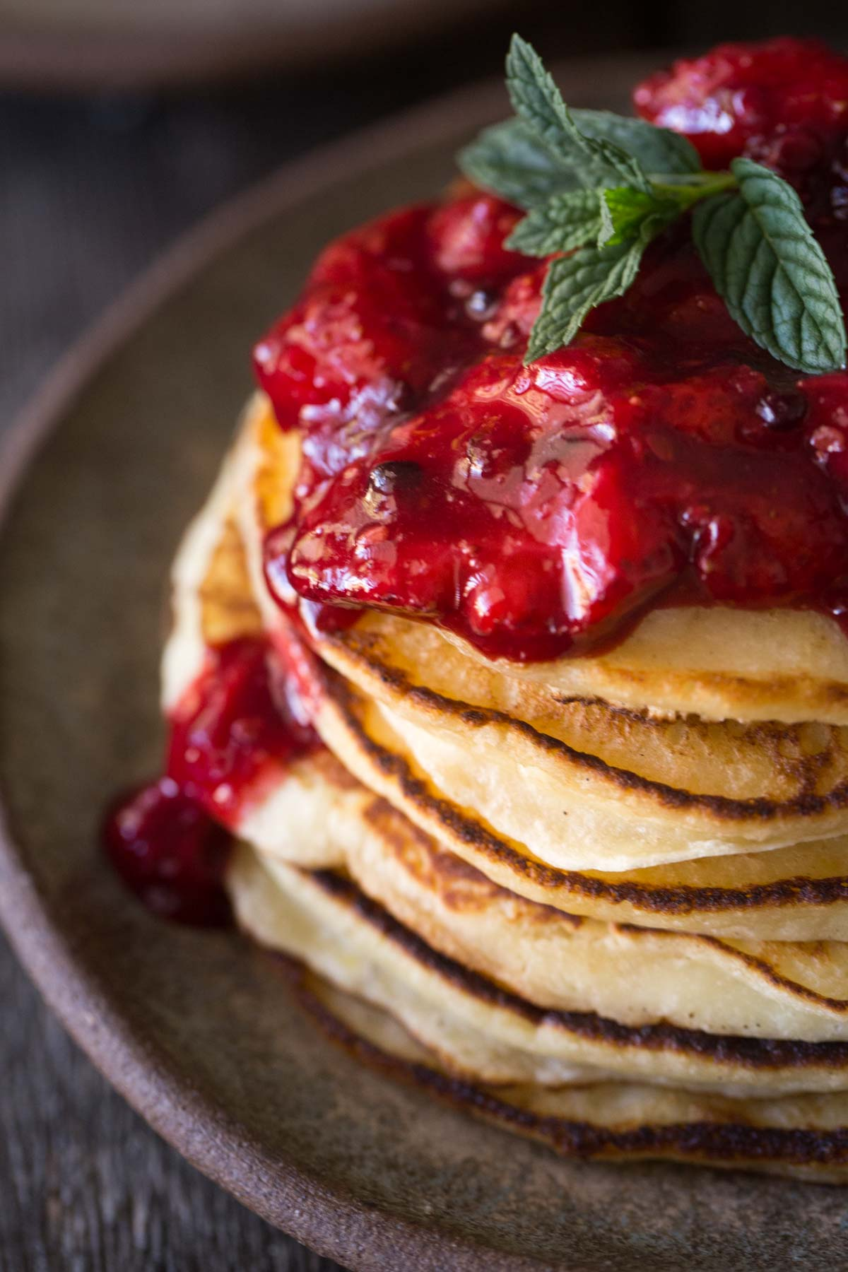 Stack of pancakes with fresh berry sauce on top and a sprig of mint.