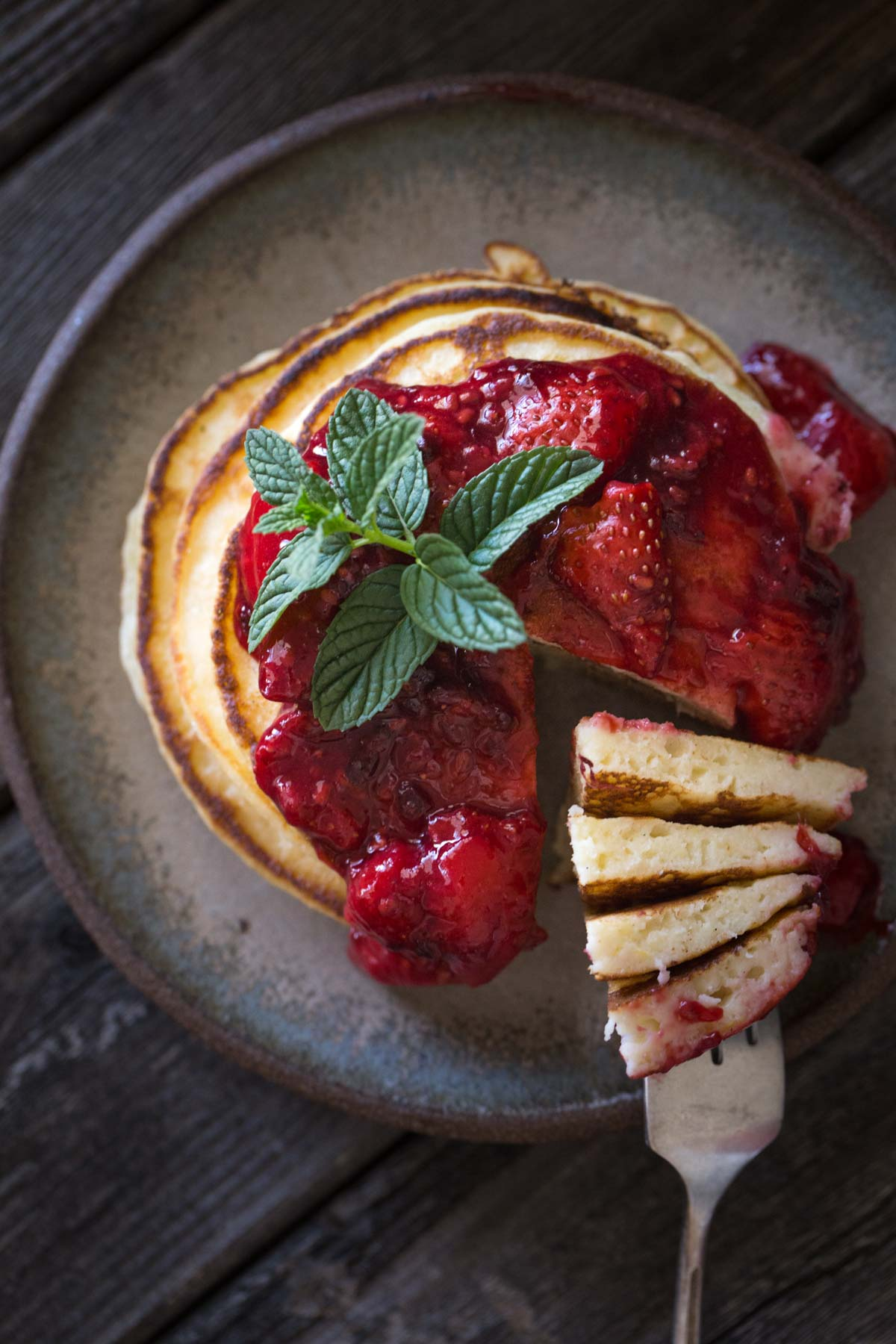A top down view of a stack of Lemon Ricotta Pancakes with Fresh Berry Sauce.
