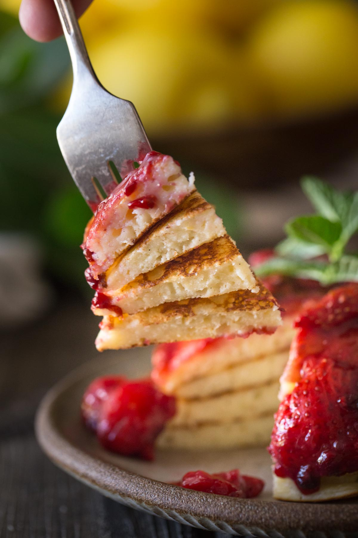 A forkful of Lemon Ricotta pancakes and fresh berry sauce.