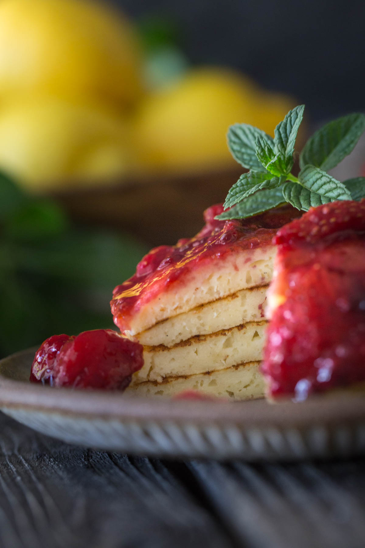 A plate of lemon ricotta pancakes with a bite cut out.