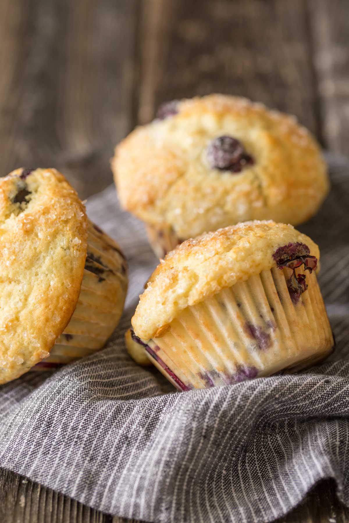 Three Best Ever Buttermilk Blueberry Muffins on a kitchen towel.