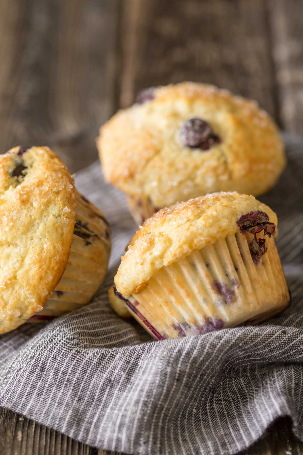 Three Best Ever Buttermilk Blueberry Muffins on a kitchen towel.