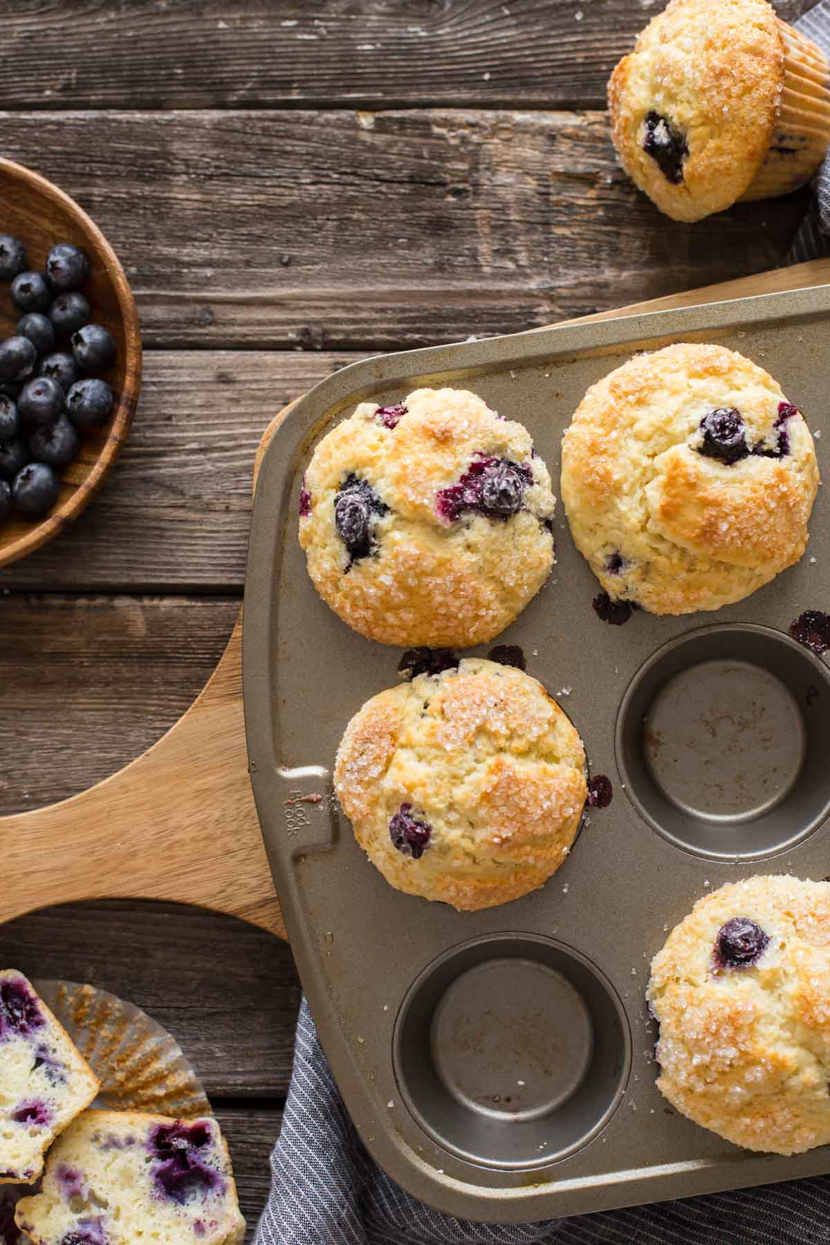 Best Ever Buttermilk Blueberry Muffins in a muffin pan on a wooden backboard with a bowl of fresh blueberries.