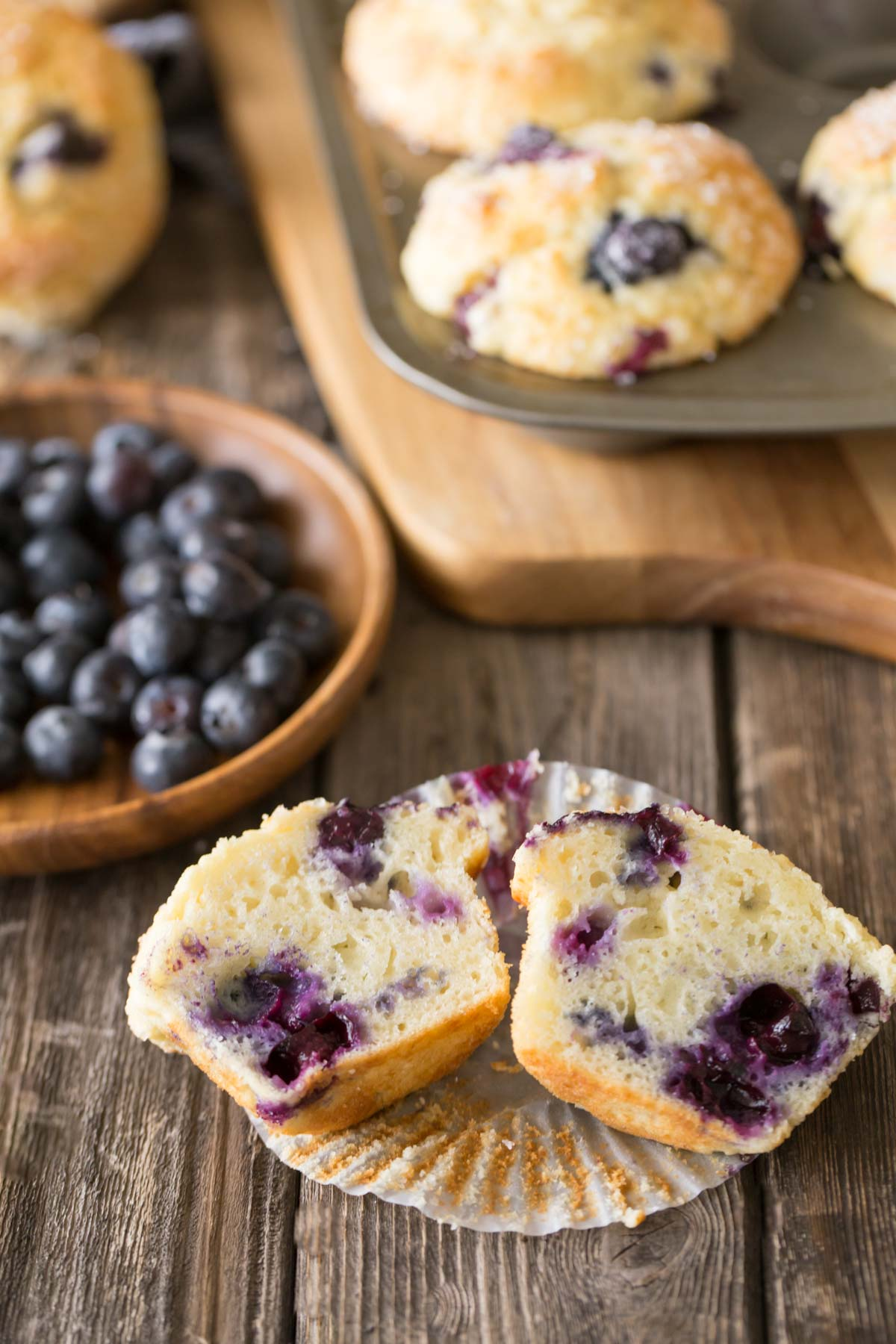 Best Ever Buttermilk Blueberry Muffins in a muffin pan with a muffin cut in half in the front of the picture.