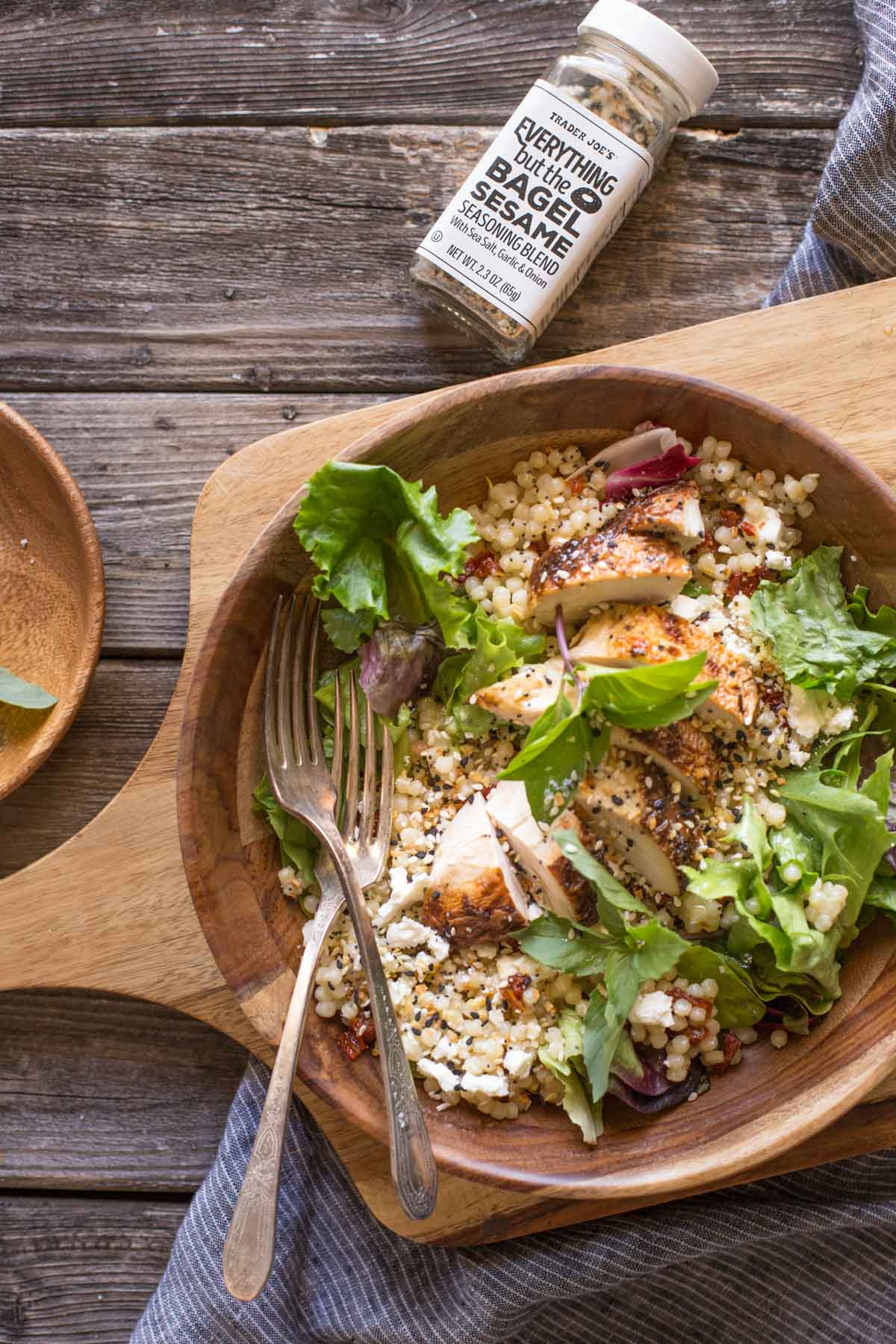 Israeli Couscous Salad with Honey Lemon Vinaigrette in a wooden bowl on a wooden cutting board with Everything But the Bagel Seasoning.