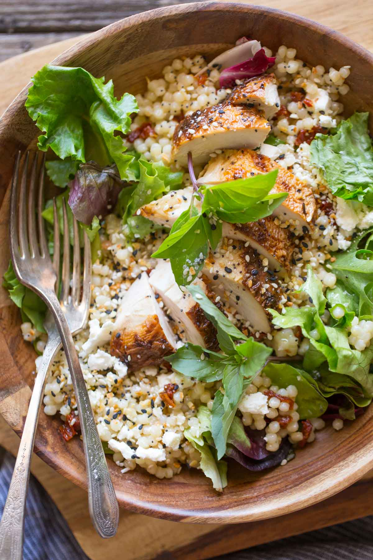 Israeli Couscous Salad with Honey Lemon Vinaigrette in a wooden bowl on a wooden cutting board.