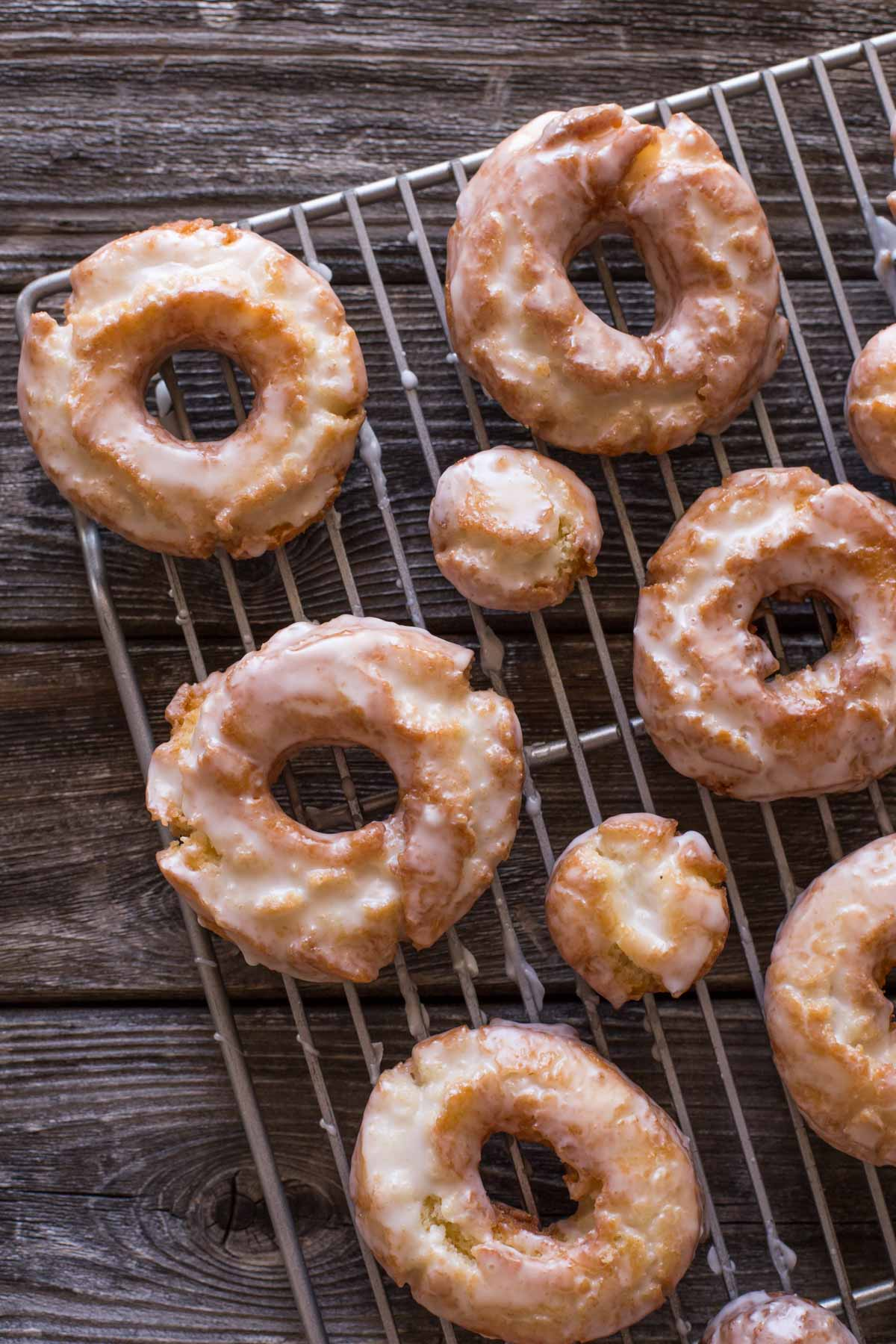 Overhead view of Old Fashioned Buttermilk Donuts on a cooking rack on a wooden background.