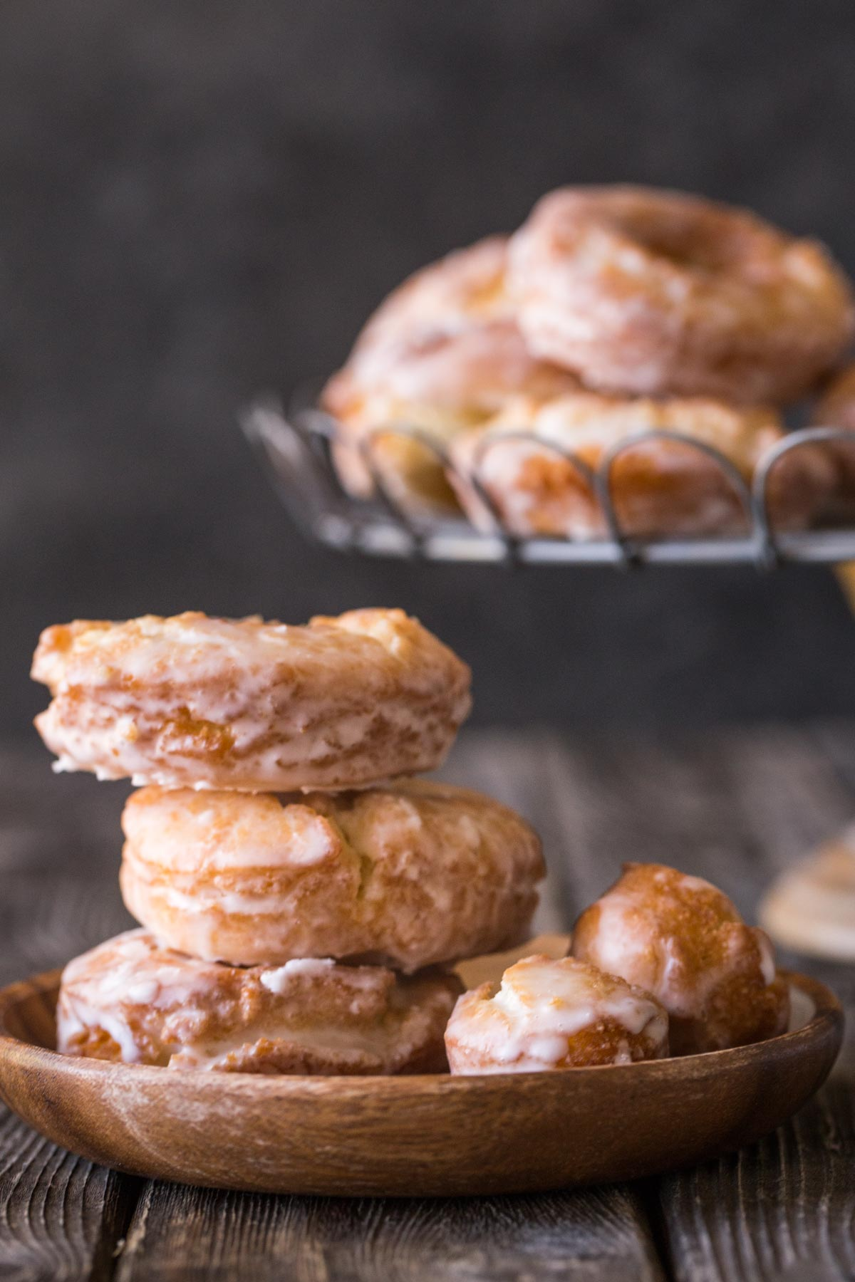 Stack of three Old Fashioned Buttermilk Donuts from the front view with a cake plate holding donuts in the background.