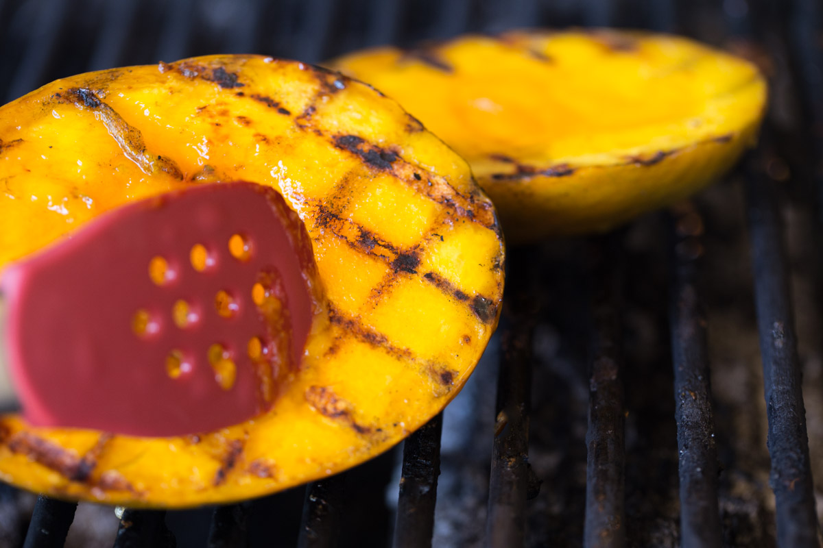 Mango halves on a grill with grill marks.
