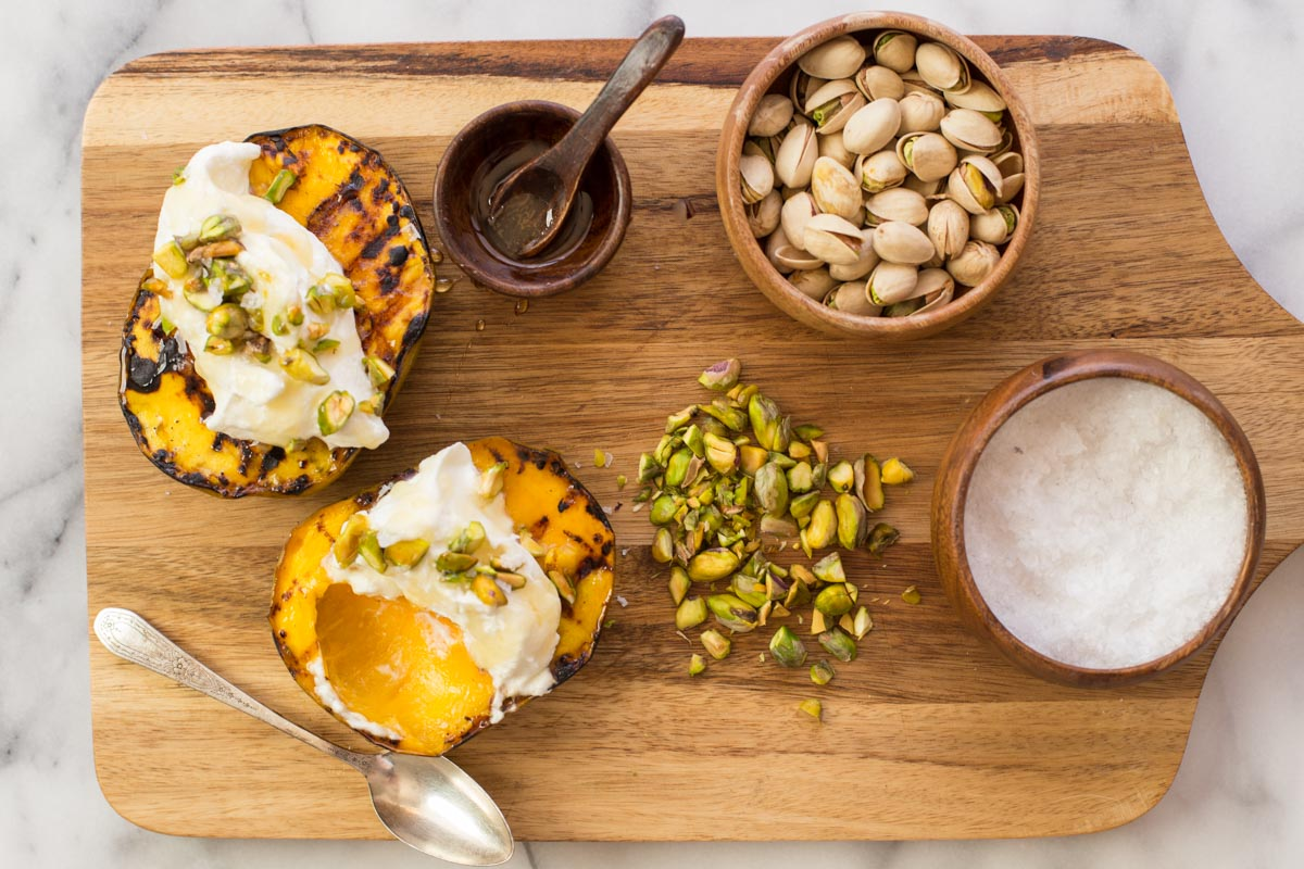Overhead shot of wooden board with Grilled Mango With Honey Ricotta Whipped Cream, sea salt, honey, and pistachios