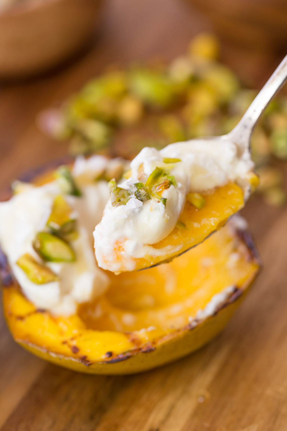 Grilled Mango With Honey Ricotta Whipped Cream with spoonful in the foreground.