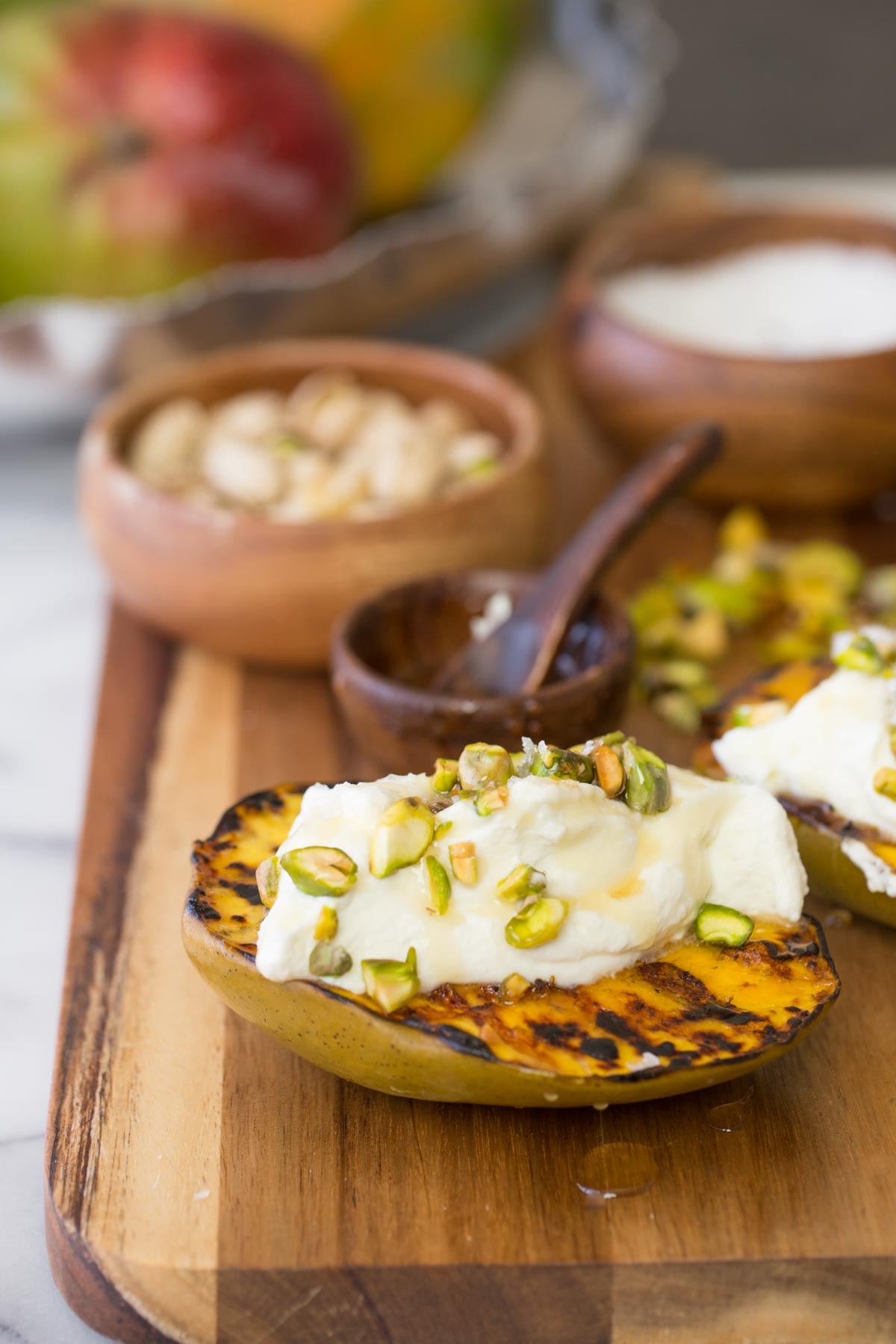 Wooden board with Grilled Mango With Honey Ricotta Whipped Cream