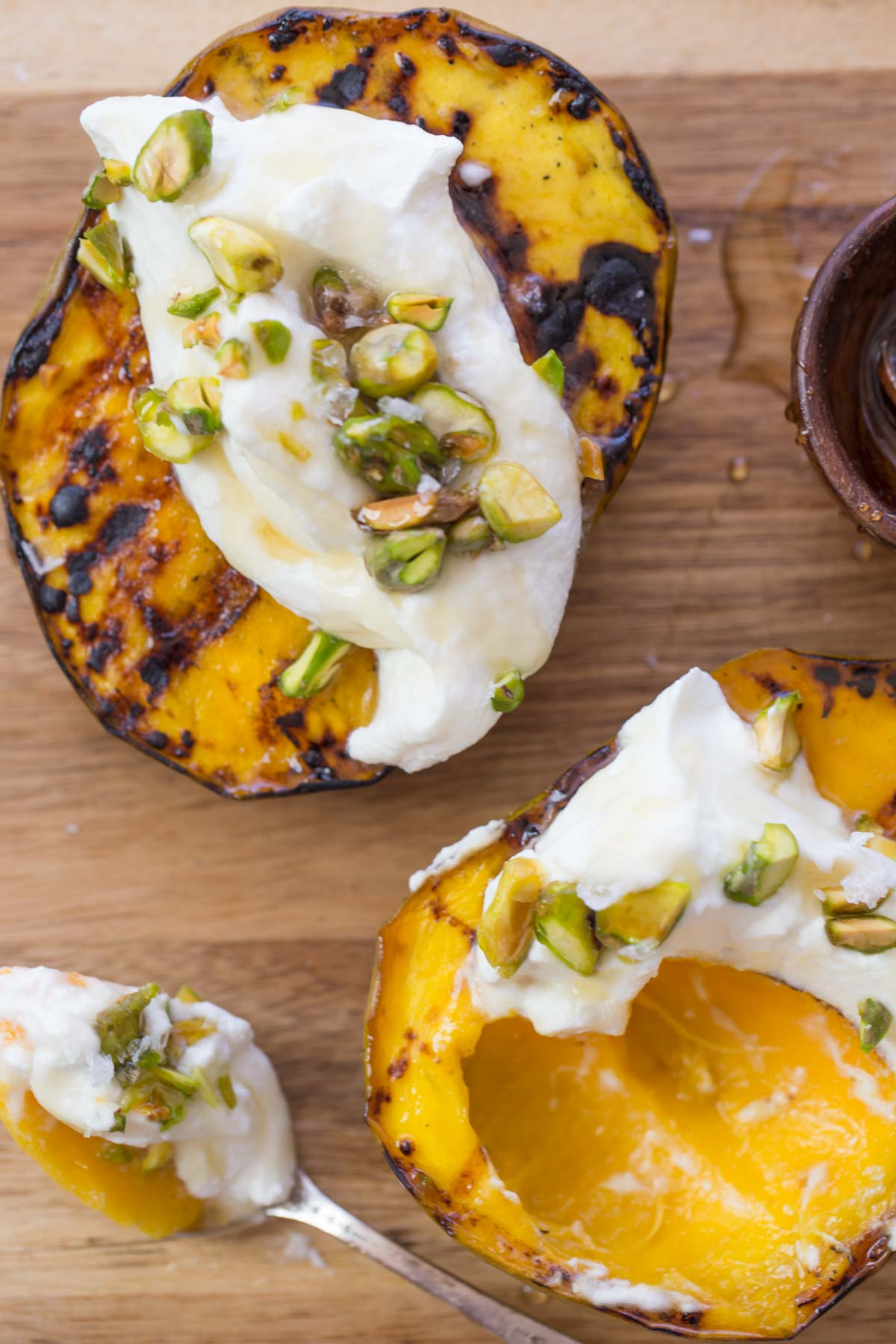Grilled Mango With Honey Ricotta Whipped Cream on a wooden board.