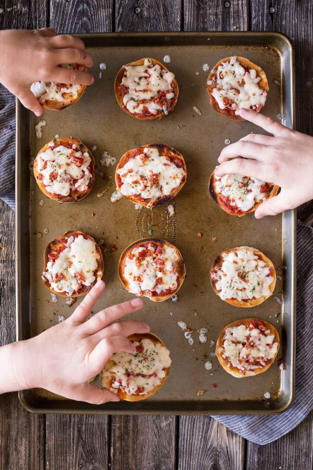 Top down view of Homemade Mini Bagel Pizzas on a baking sheet with hands reaching in.