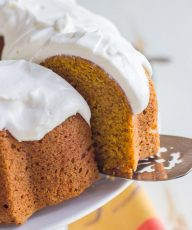 A close up view of a slice of pumpkin spice bundt cake on a cake serve.