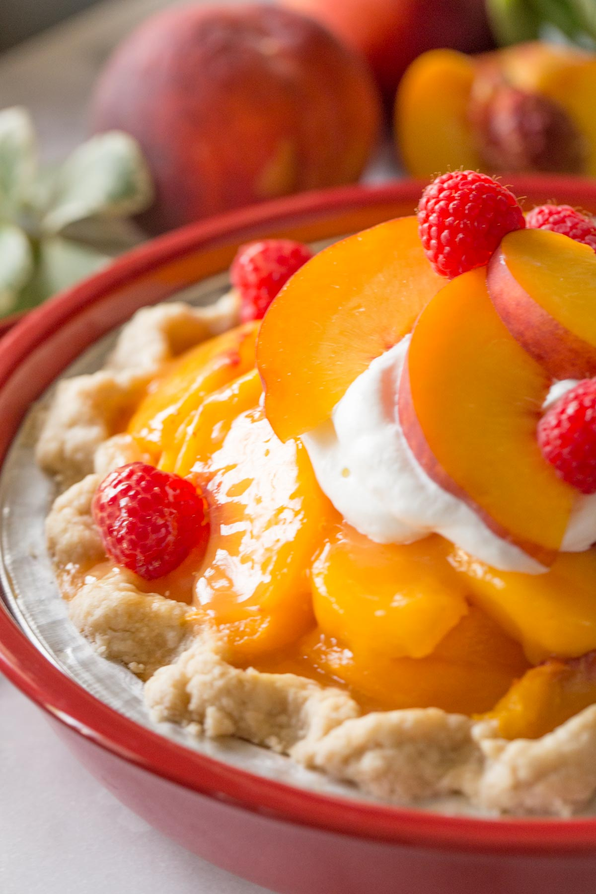 A close up shot of Fresh peach pie with homemade whipped cream in a red pie dish on a white marble background.