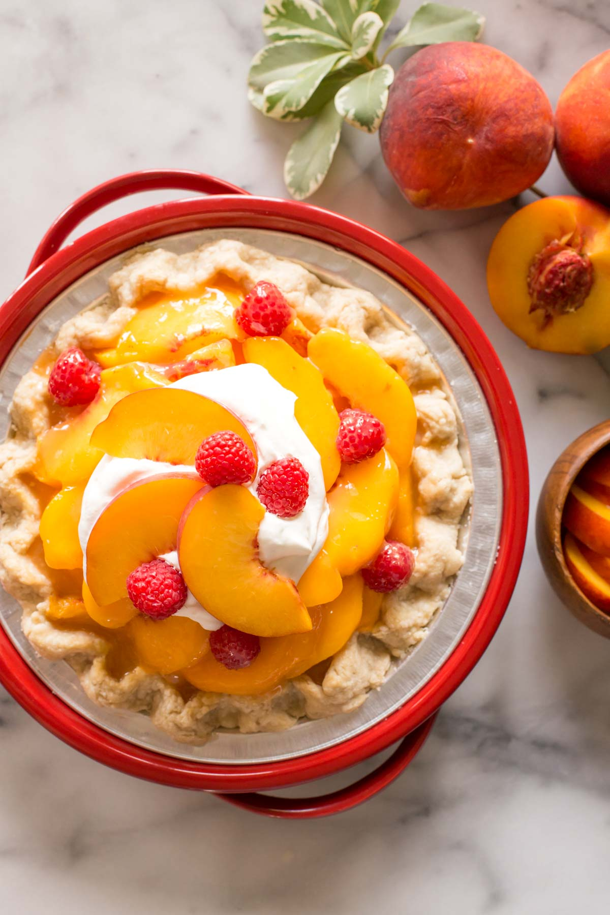 Fresh peach pie with homemade whipped cream in a red pie dish on a white marble background.