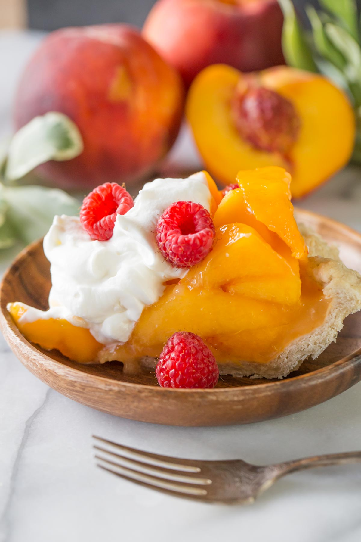 Fresh peach pie with homemade whipped cream in a red pie dish with whole peaches in the background.