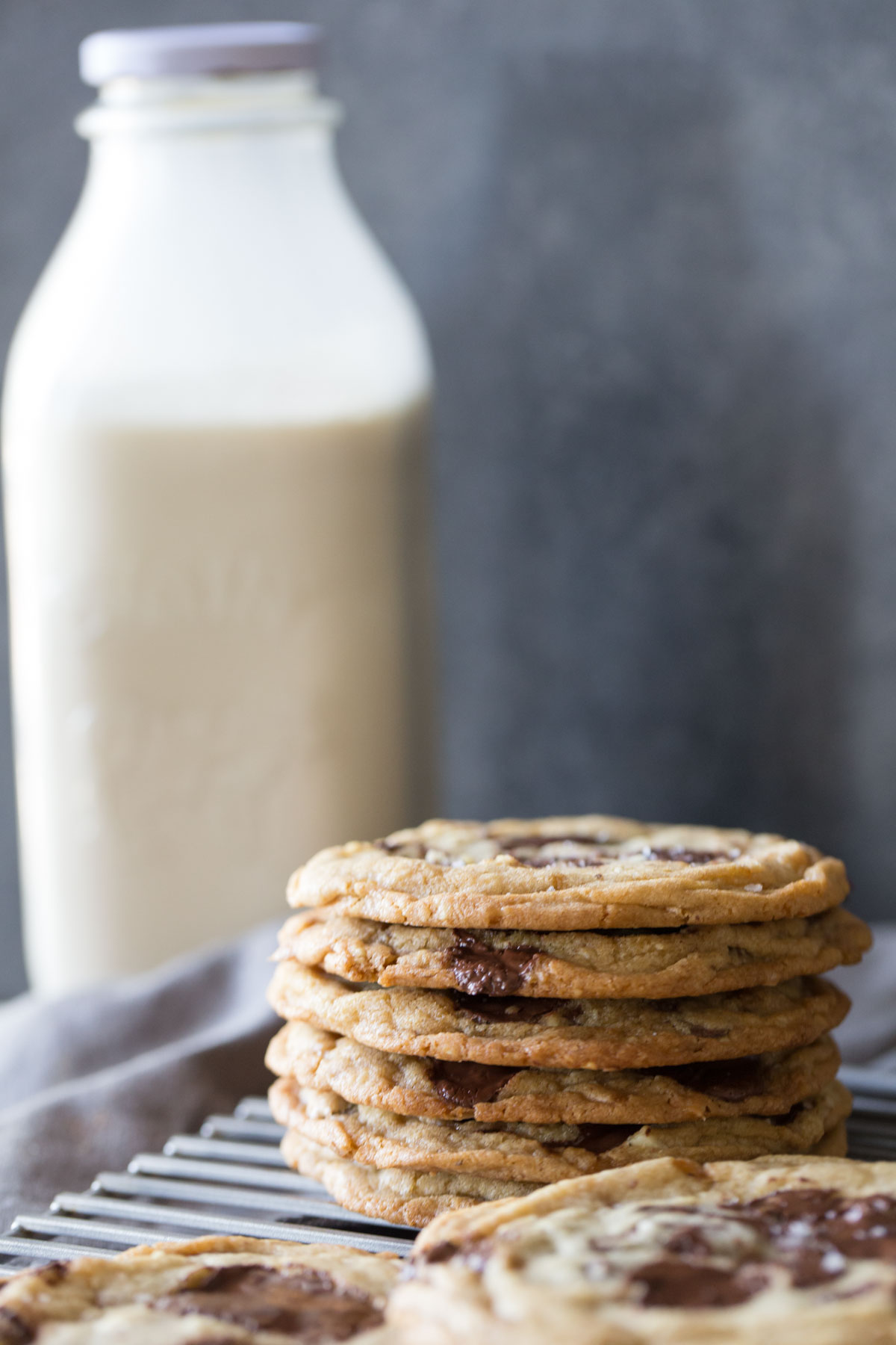 Toffee Almond Chocolate Chunk Cookies on a cooling rack with a bottle of milk in the background.