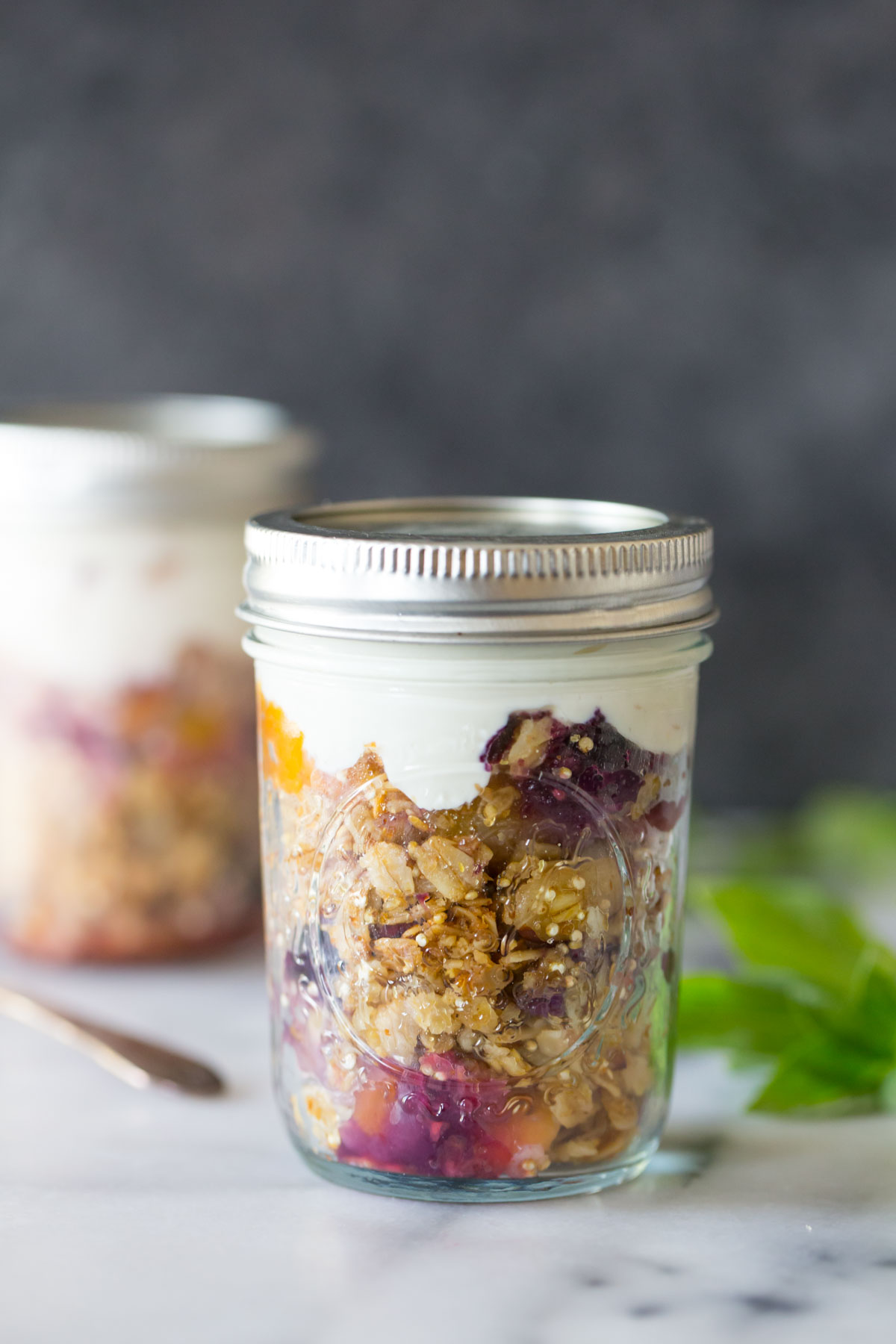 Mango Berry Breakfast Crisp in a mason jar topped with yogurt.