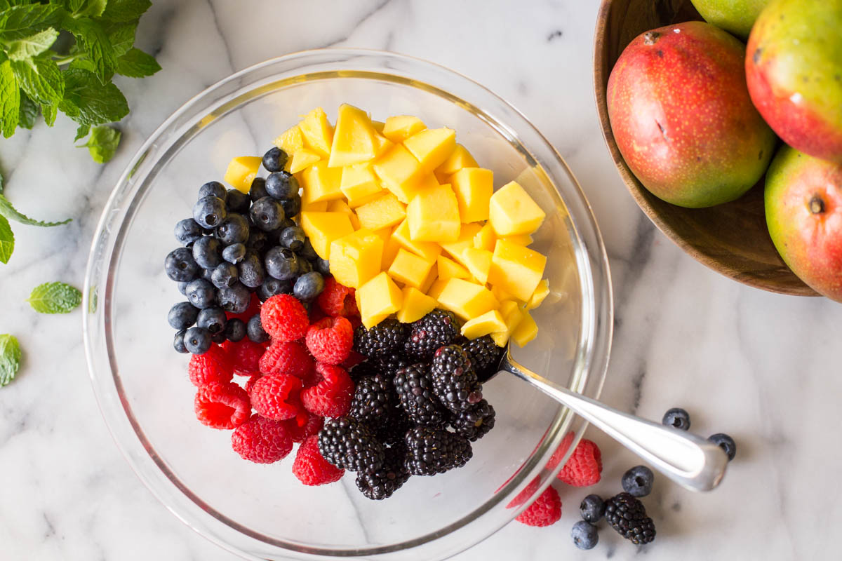 Fresh mango and berries in a glass bowl on a marble slab.