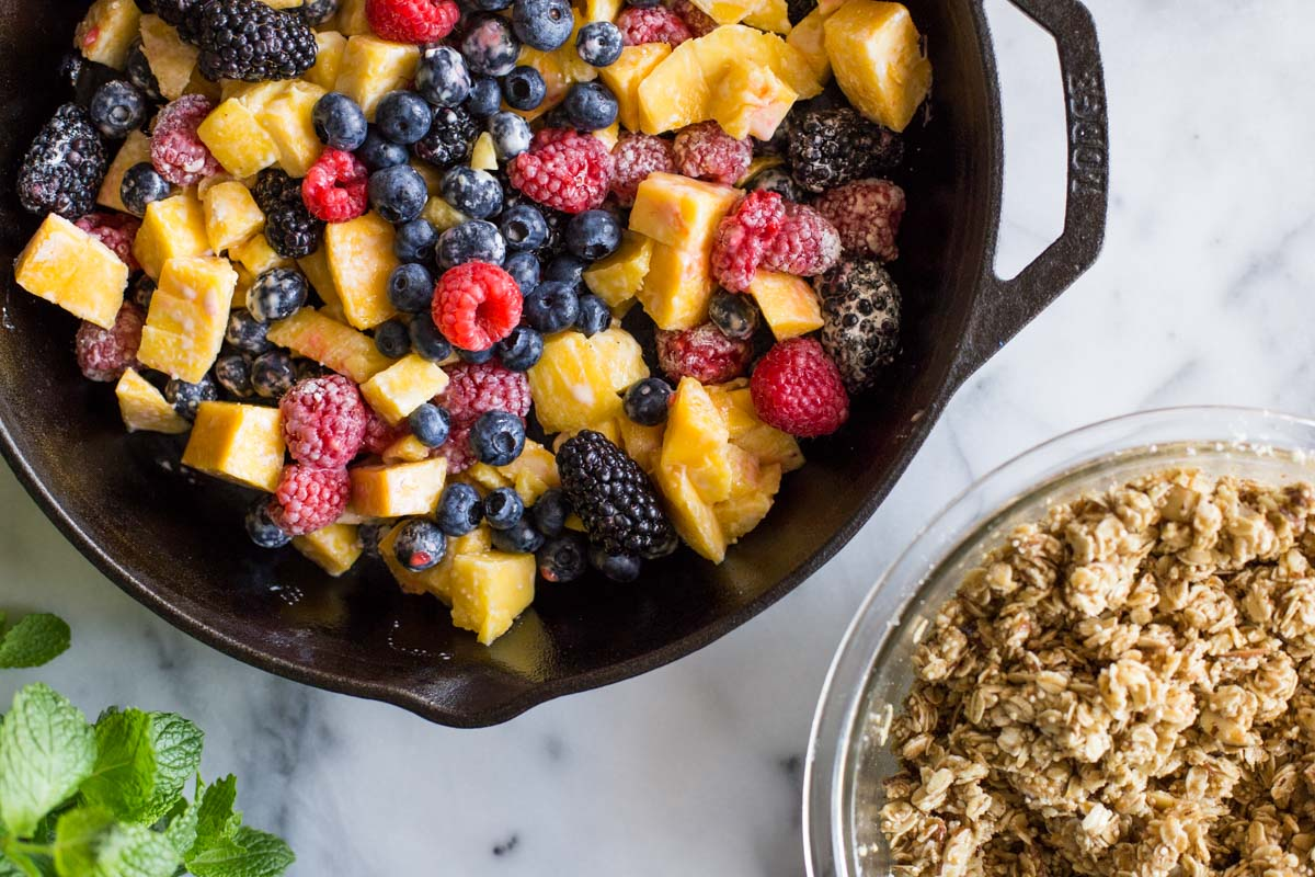 Mango and berries in a cast iron skillet ready to bake.