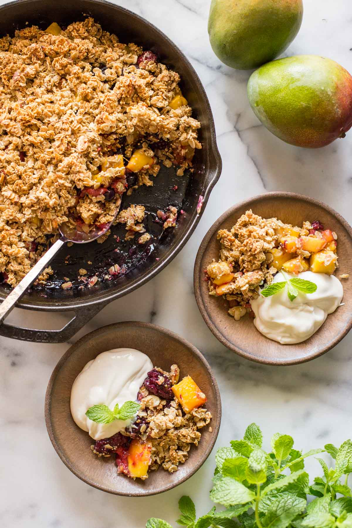 Mango Berry Breakfast Crisp in a cast iron skillet, with two bowls ready to serve.