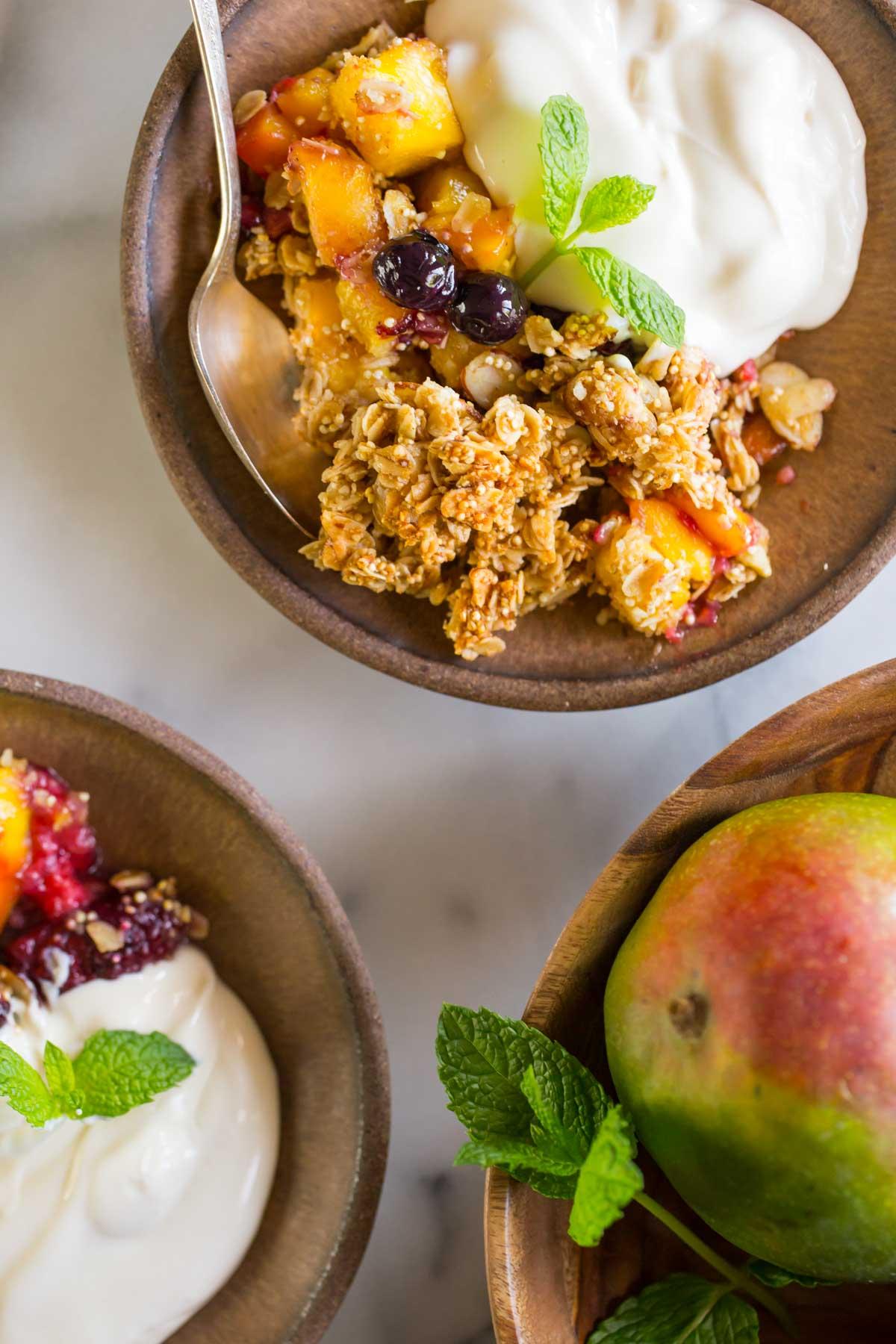 Mango Berry Breakfast Crisp in two serving bowls with yogurt.