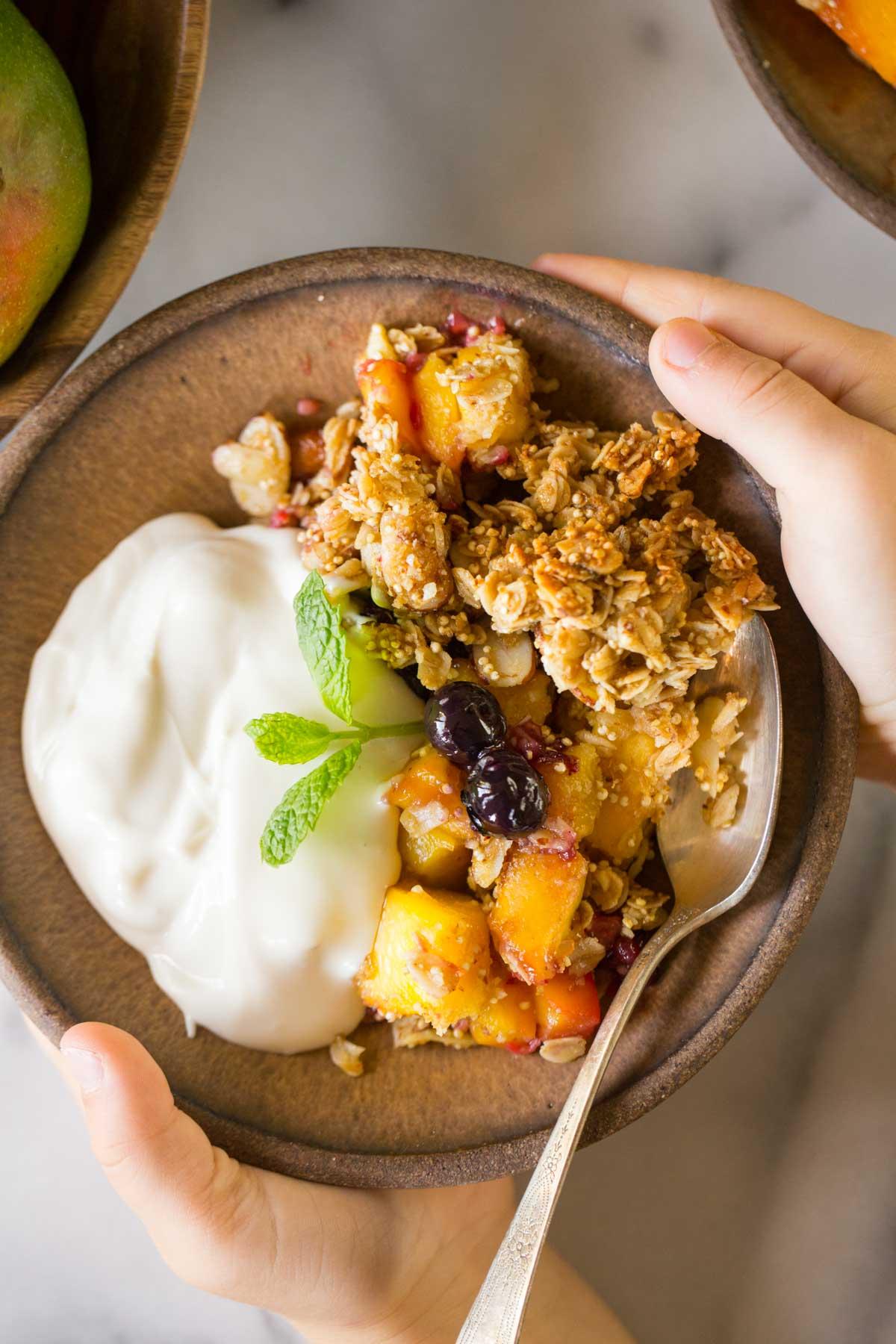 Mango Berry Breakfast Crisp on in a bowl with a side of yogurt.