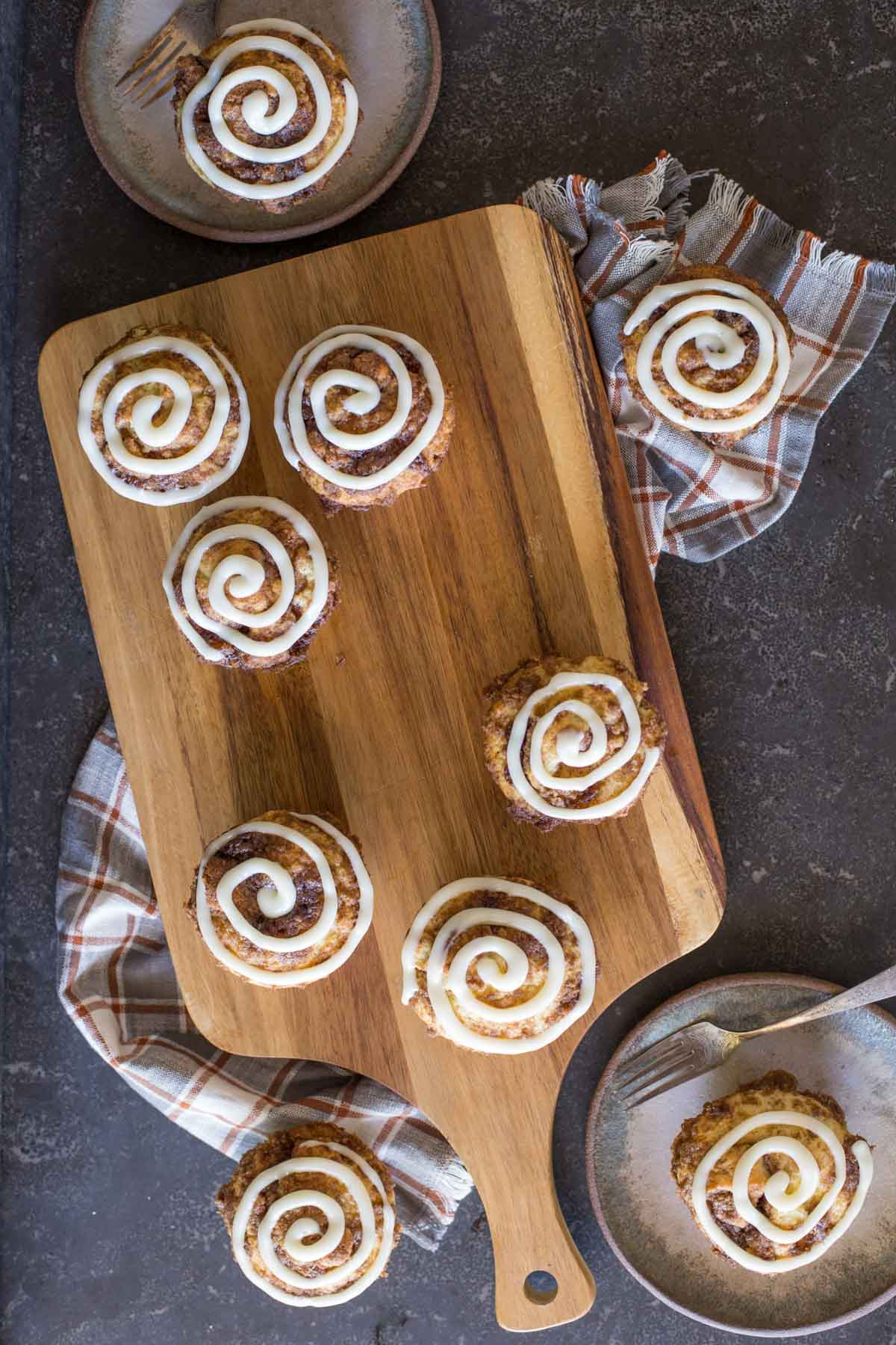 Cinnamon Roll Muffins with a cream cheese icing swirl on a wooden cutting board.