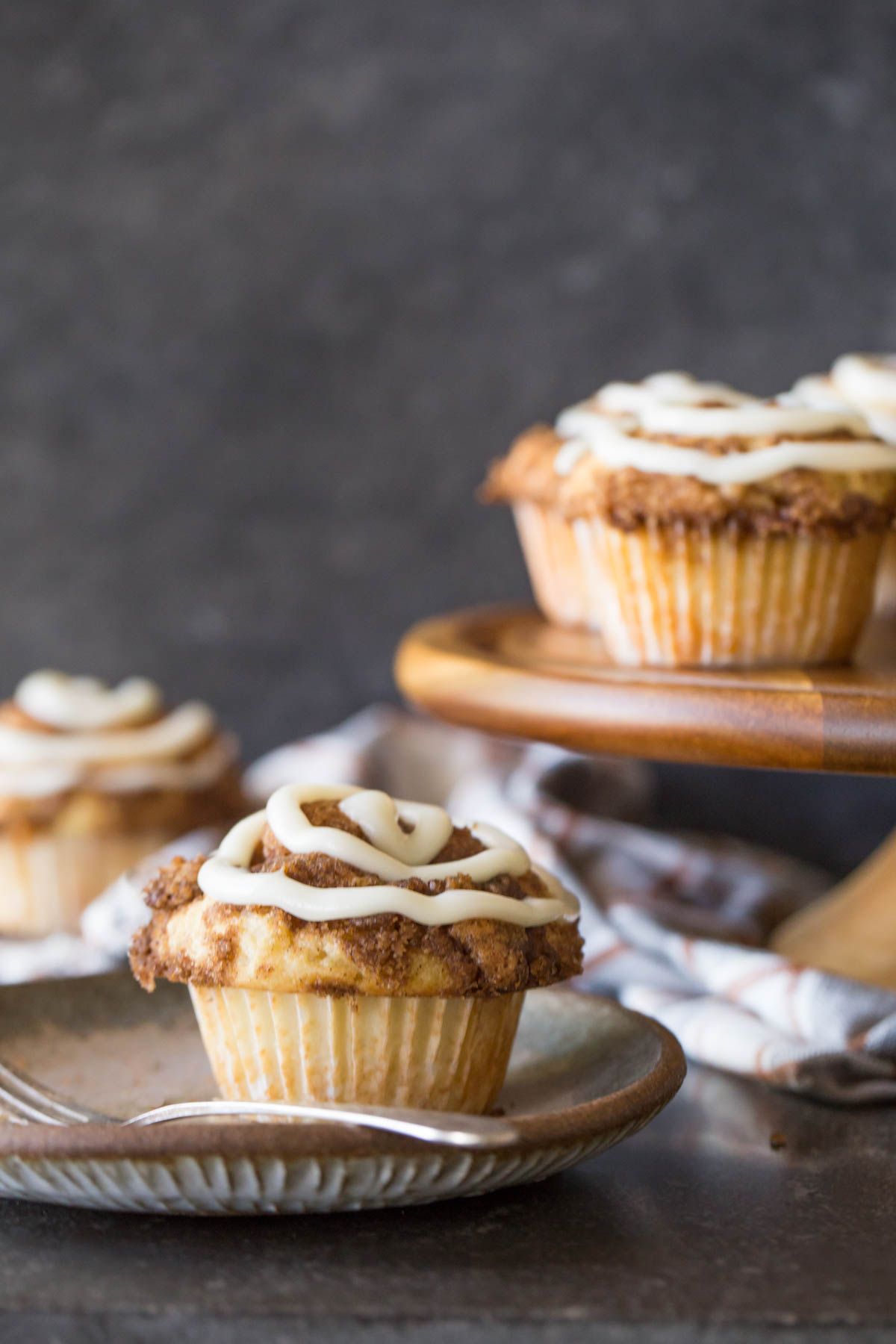 Cinnamon Roll Muffins with a cream cheese icing swirl on a grey plate with a fork.