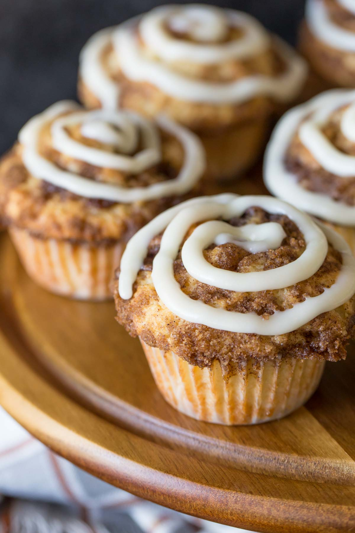 Cinnamon Roll Muffins with a cream cheese icing swirl on a wooden cake stand.